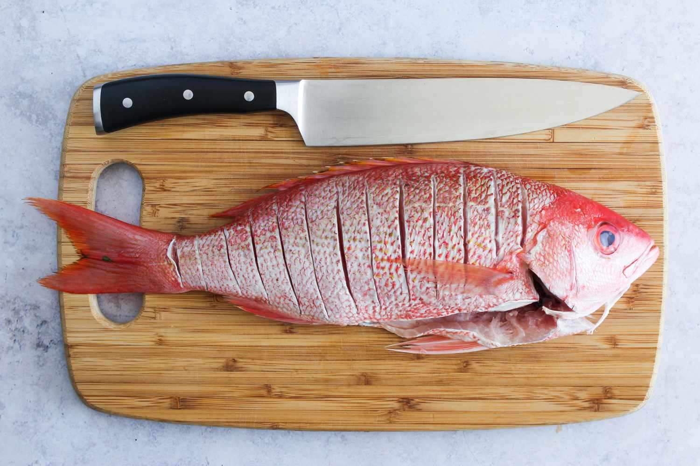 Scored fish on cutting board