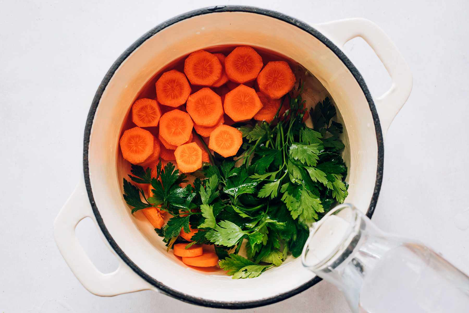 cold water, carrots, and parsley in a pot