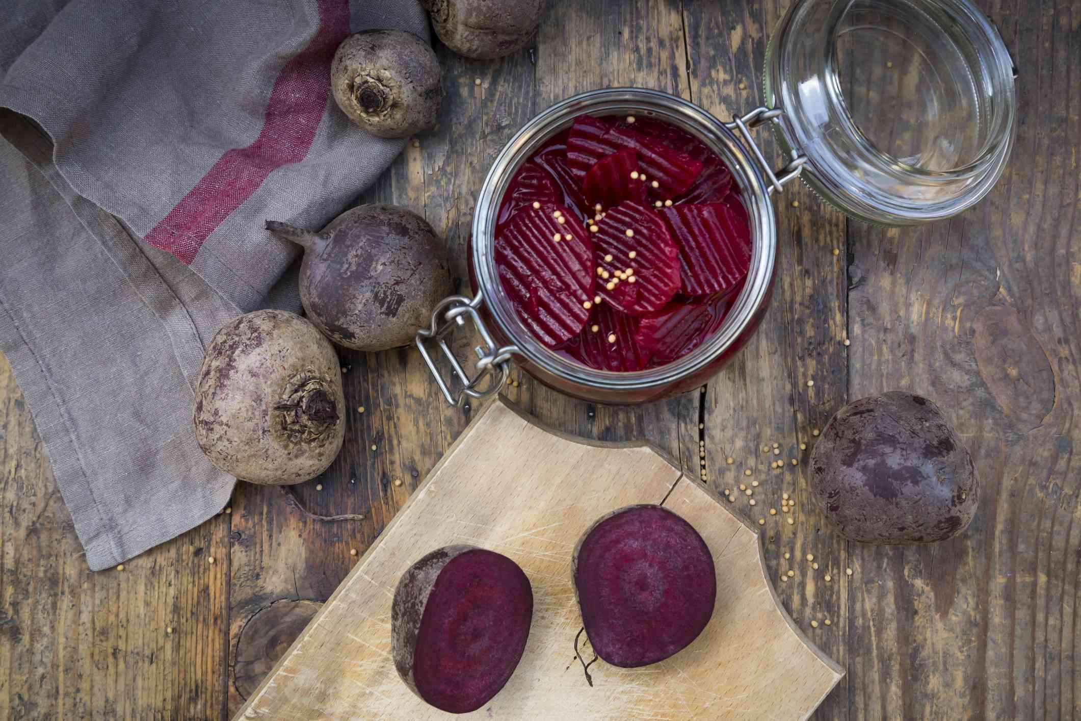 Preserving jar of pickled beetroots and whole and sliced beetroots on wood