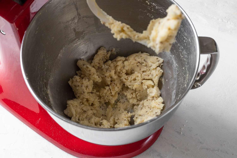 Pan de muerto dough mixed with a dough hook in a stand mixer
