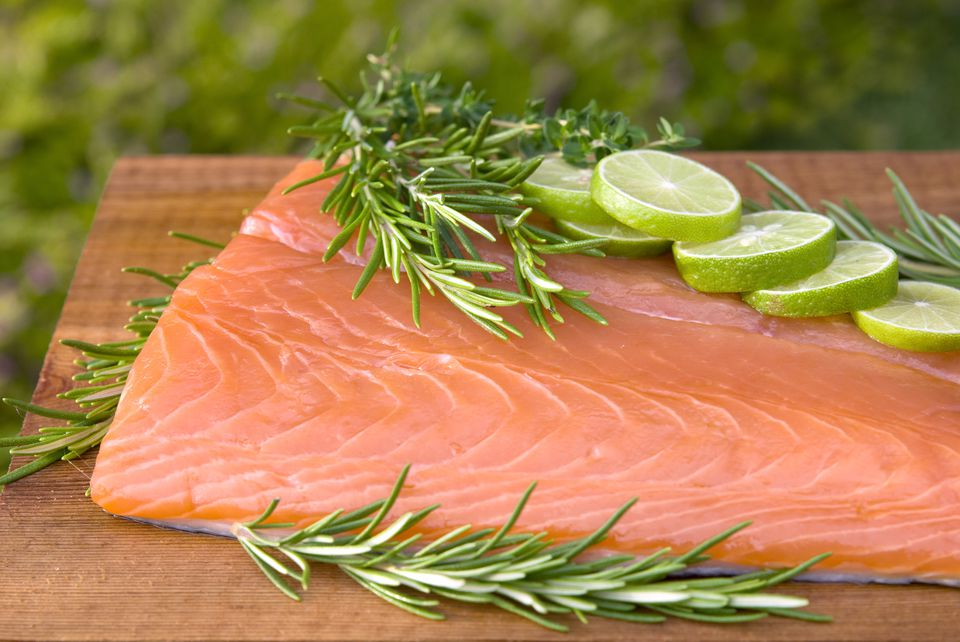 Fresh wild King salmon fish fillet, rosemary & lime on cedar plank