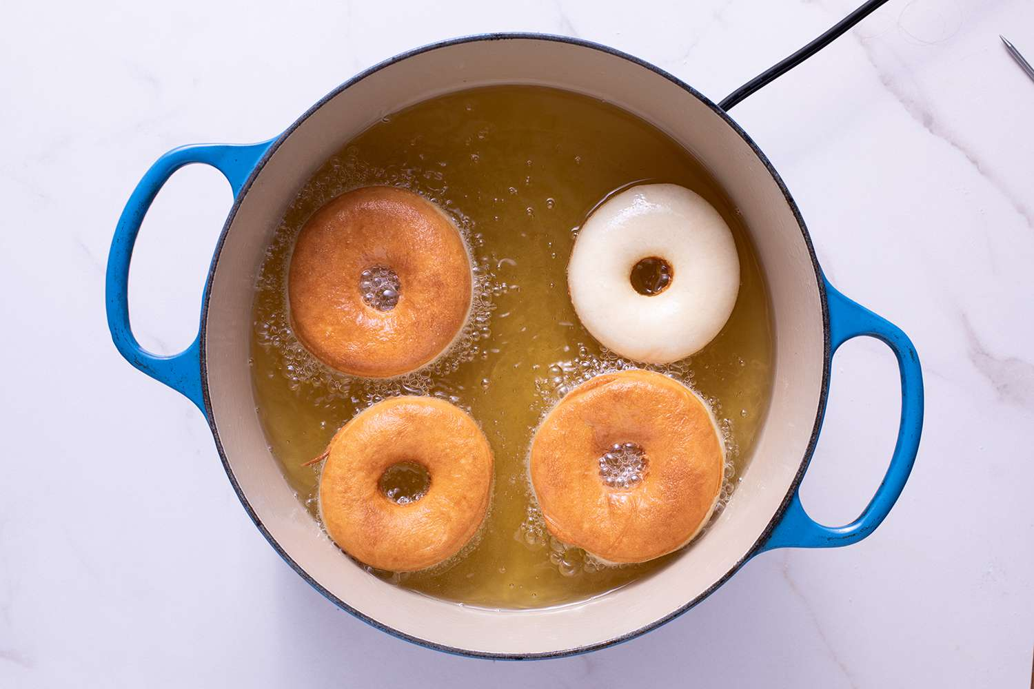 donuts frying in a pot of oil