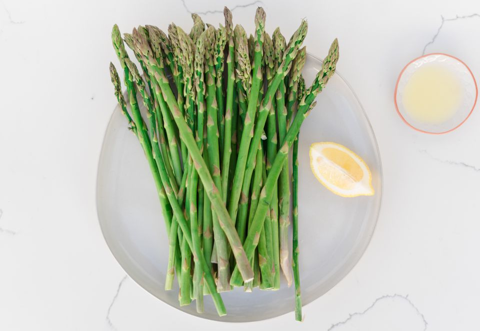 plate of asparagus with a lemon wedge