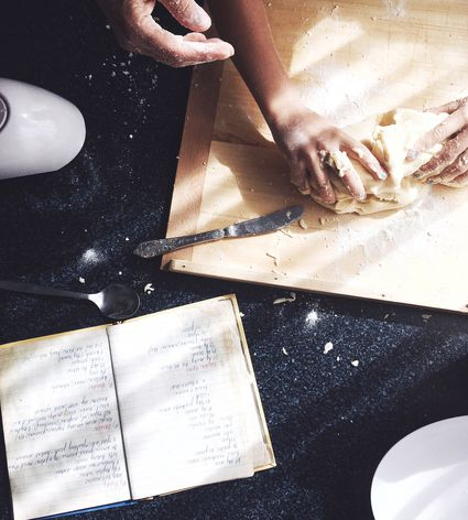 High Angle View Of Adult and Child Kneading Dough