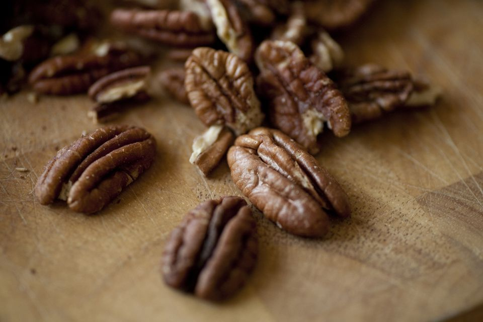 Freshly roasted organic pecans sit on a cutting board