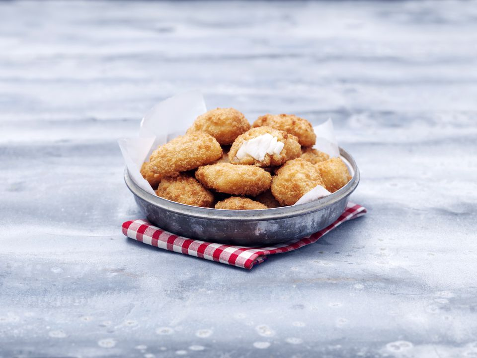 Bowl of fried chunky cod breaded nuggets on steel table