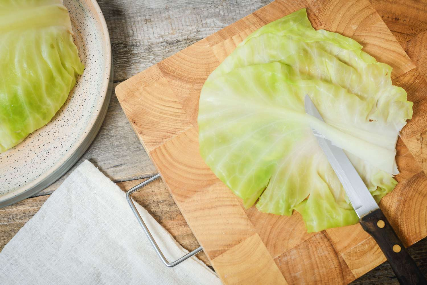 Stems removed from cabbage leaves on a cutting board