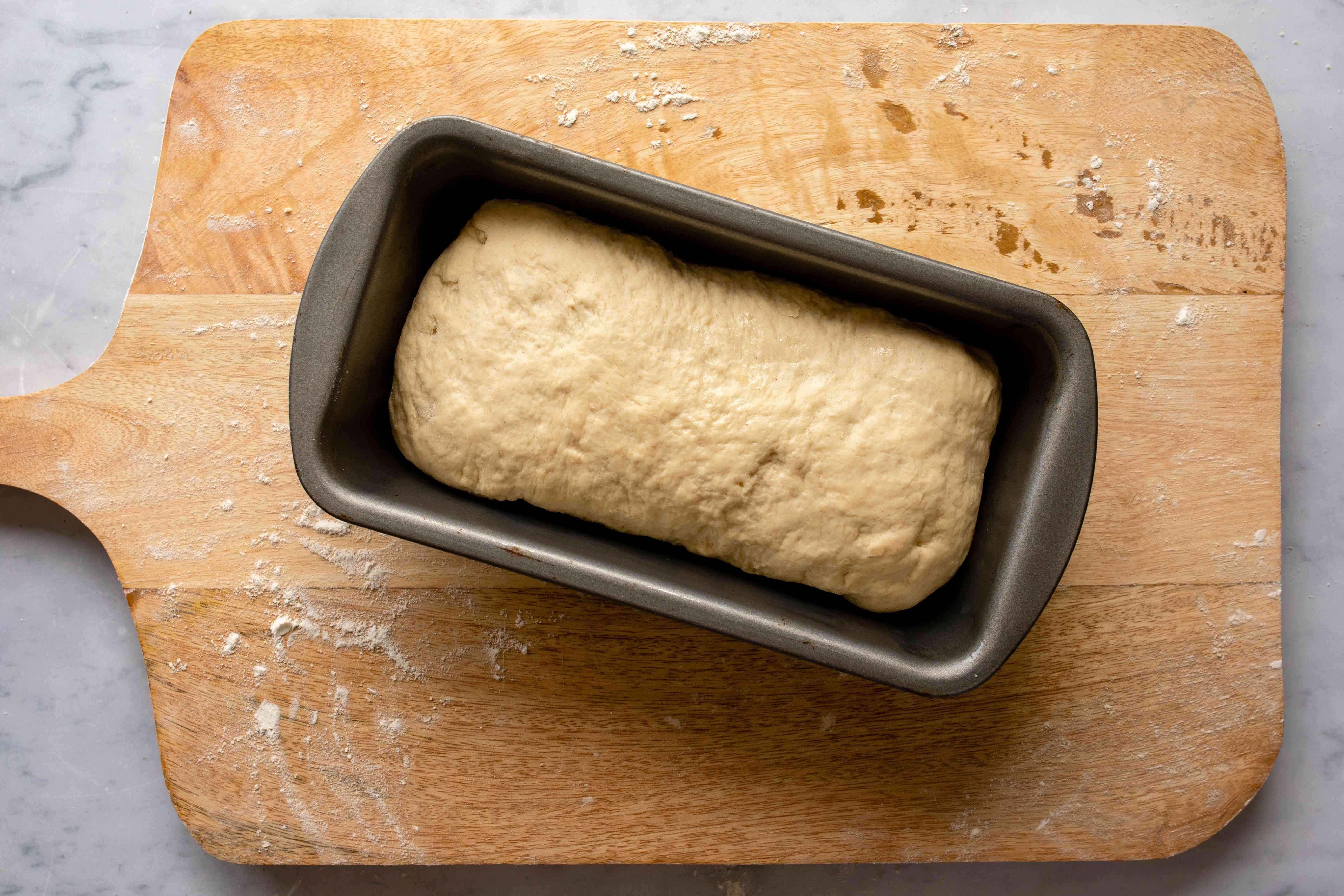 The dough in a metal bread pan