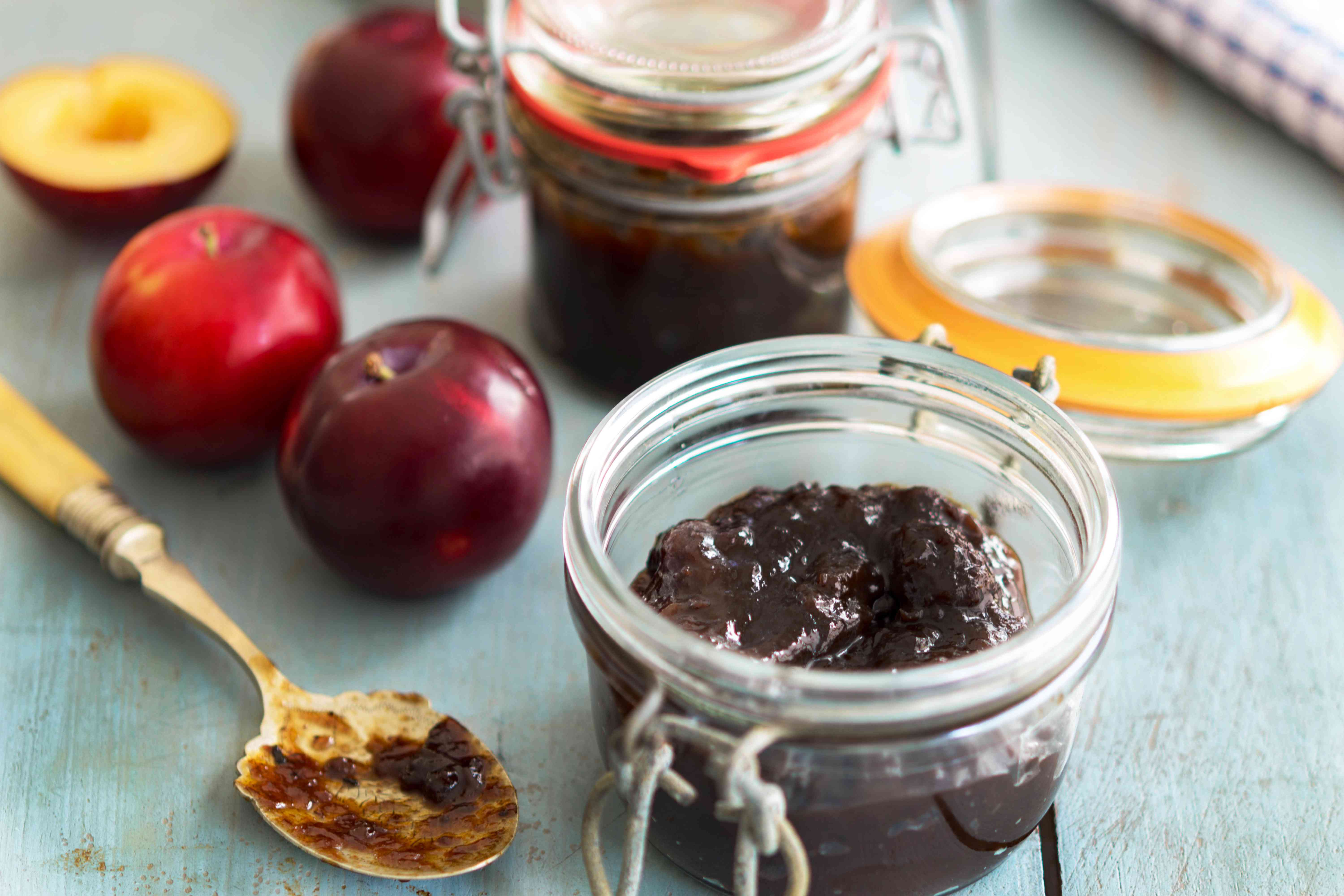 Traditional plum chutney in a canning jar with a side of fresh fruit