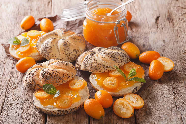 Kumquat jam in a glass jar and sweet sandwiches close-up.
