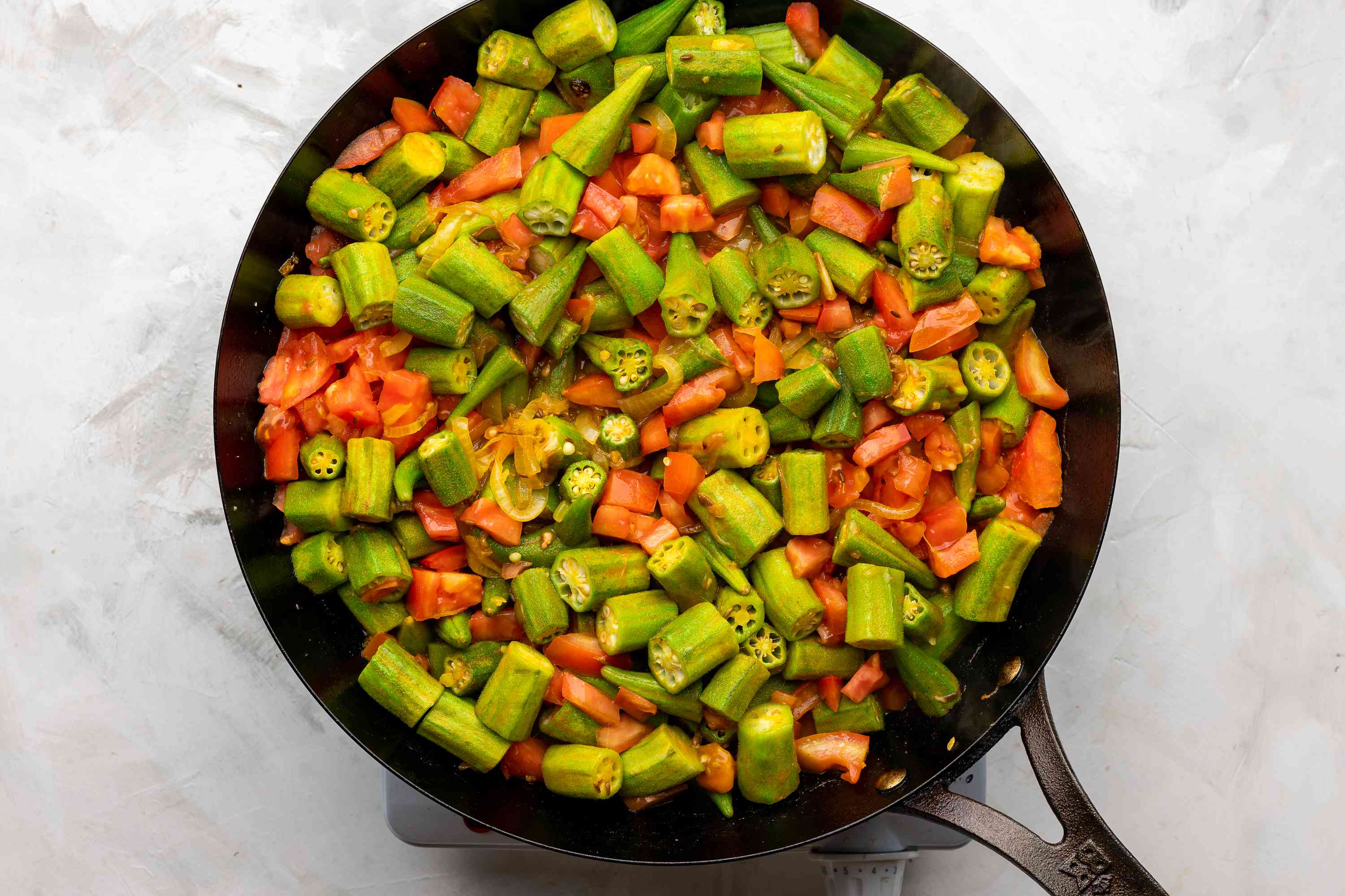 okra, onions and tomatoes in a pan