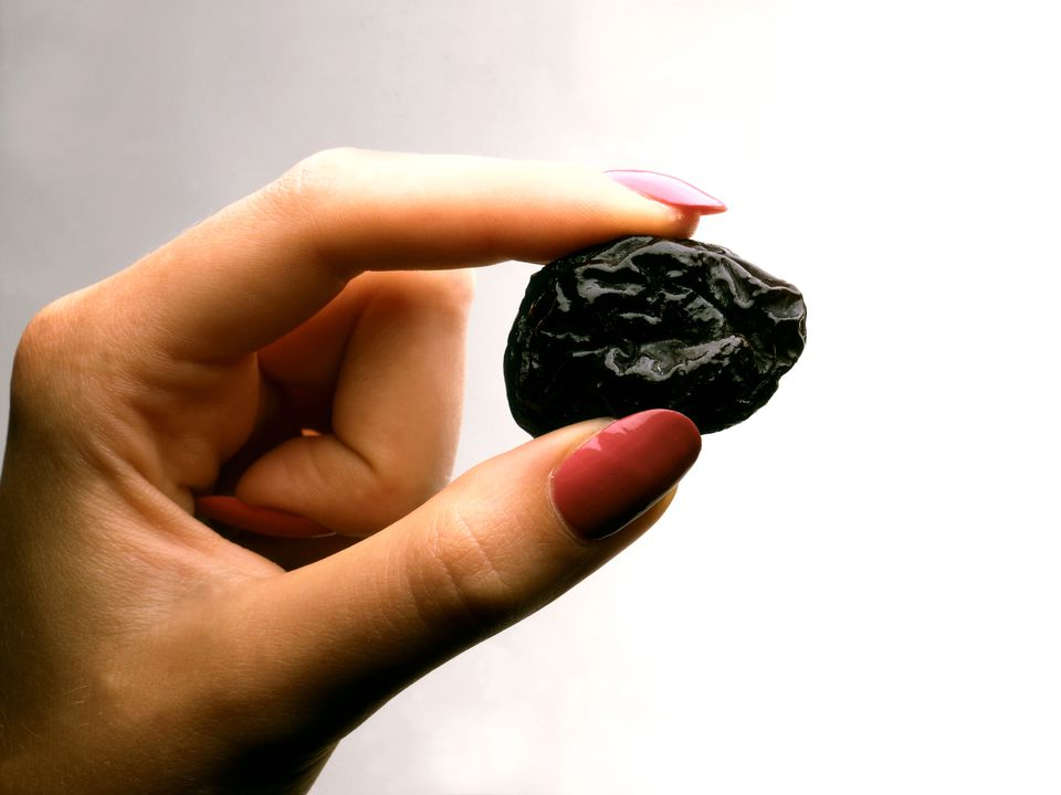 A woman holding a prune