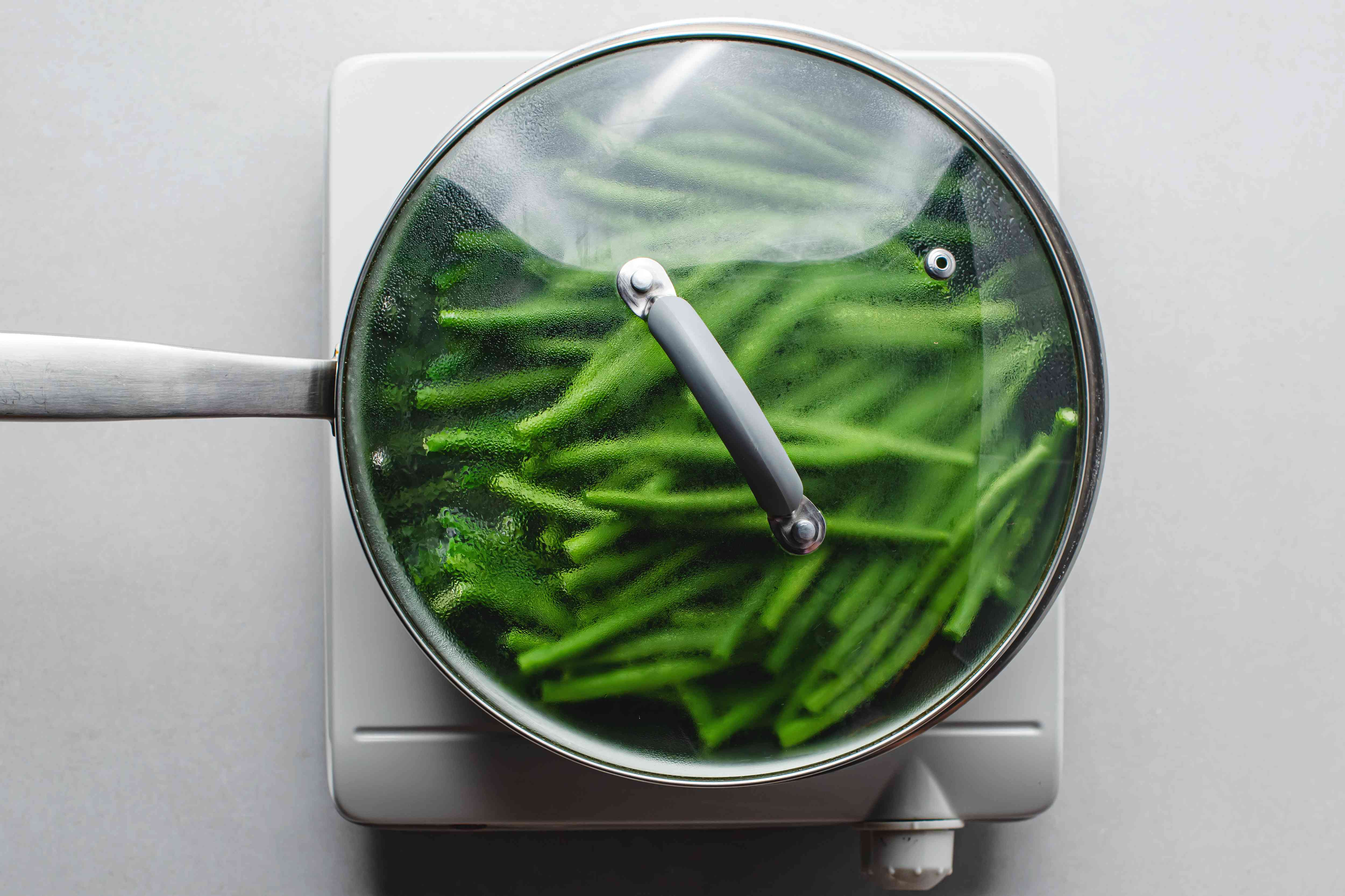 green beans cooking in a covered saucepan