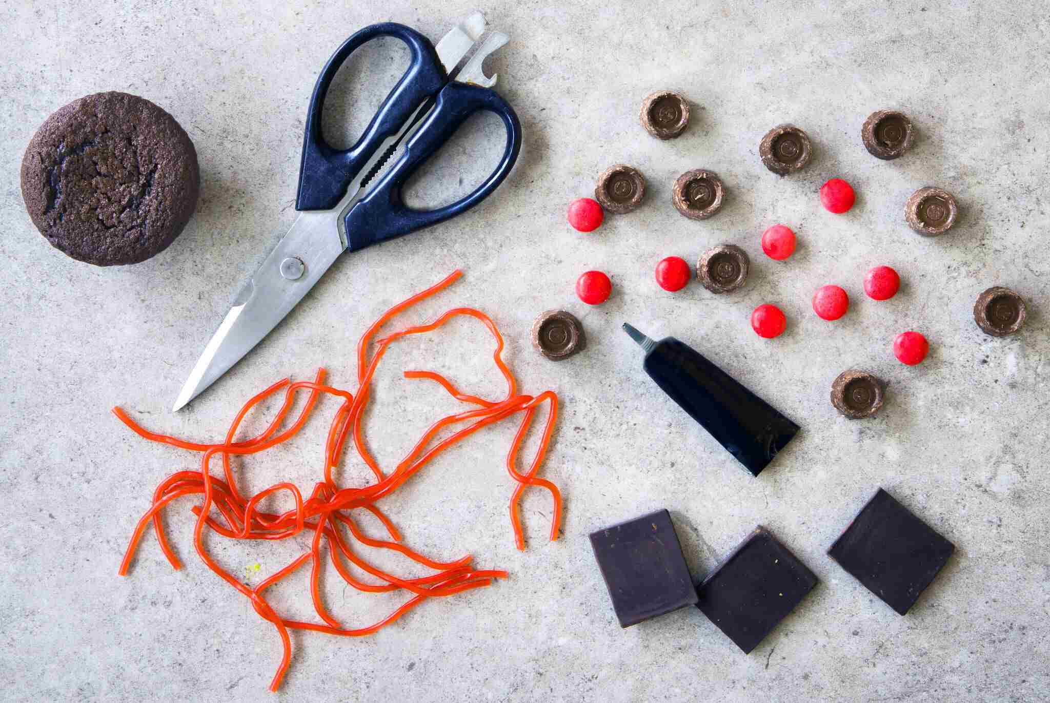 Ingredients to make graduation cap cupcakes are gathered on a work surface