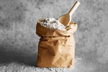 A bag of flour with a wooden spoon.