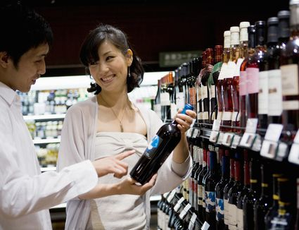 Young couple chooses wine in shop