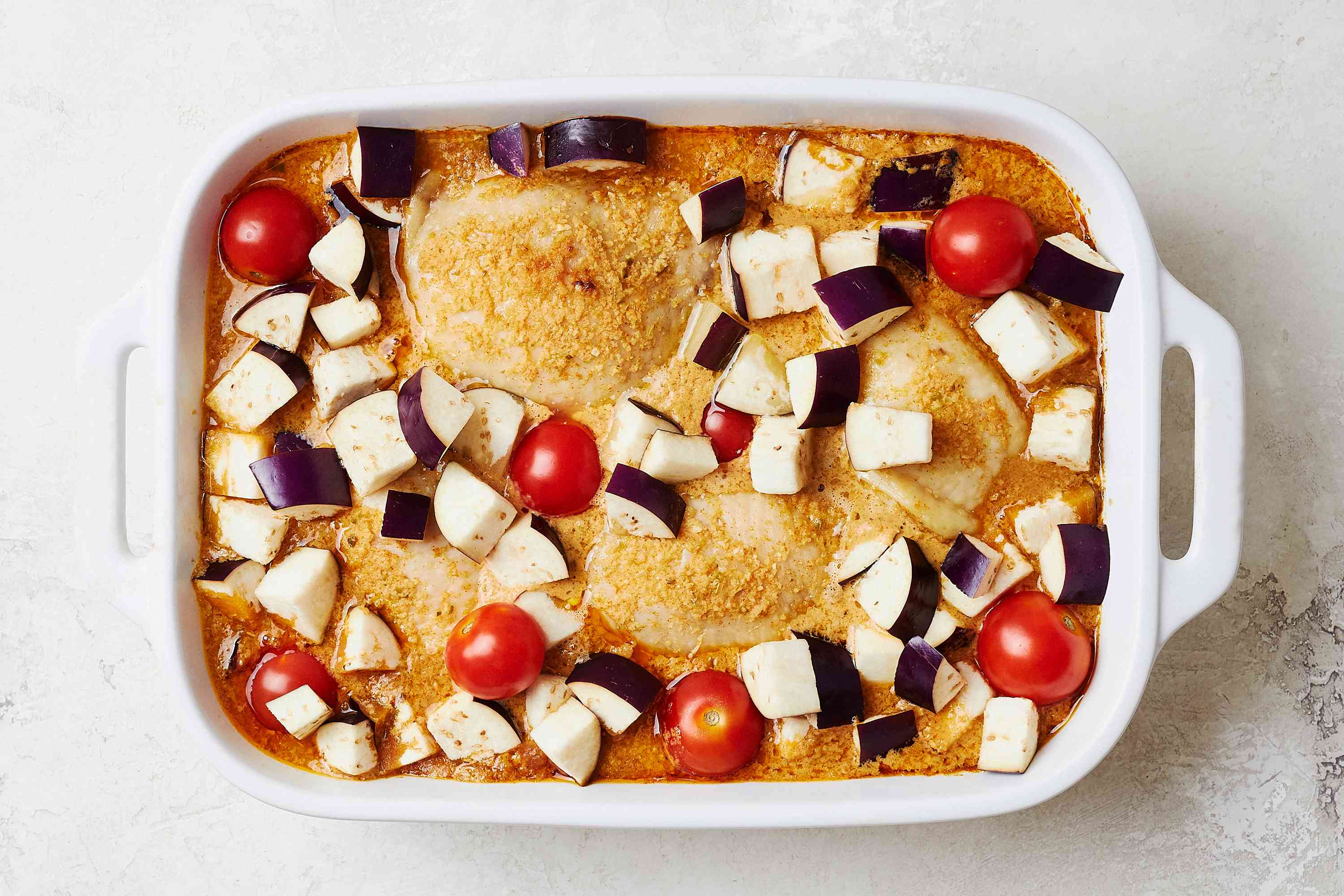 chicken with curry and vegetables in a baking dish