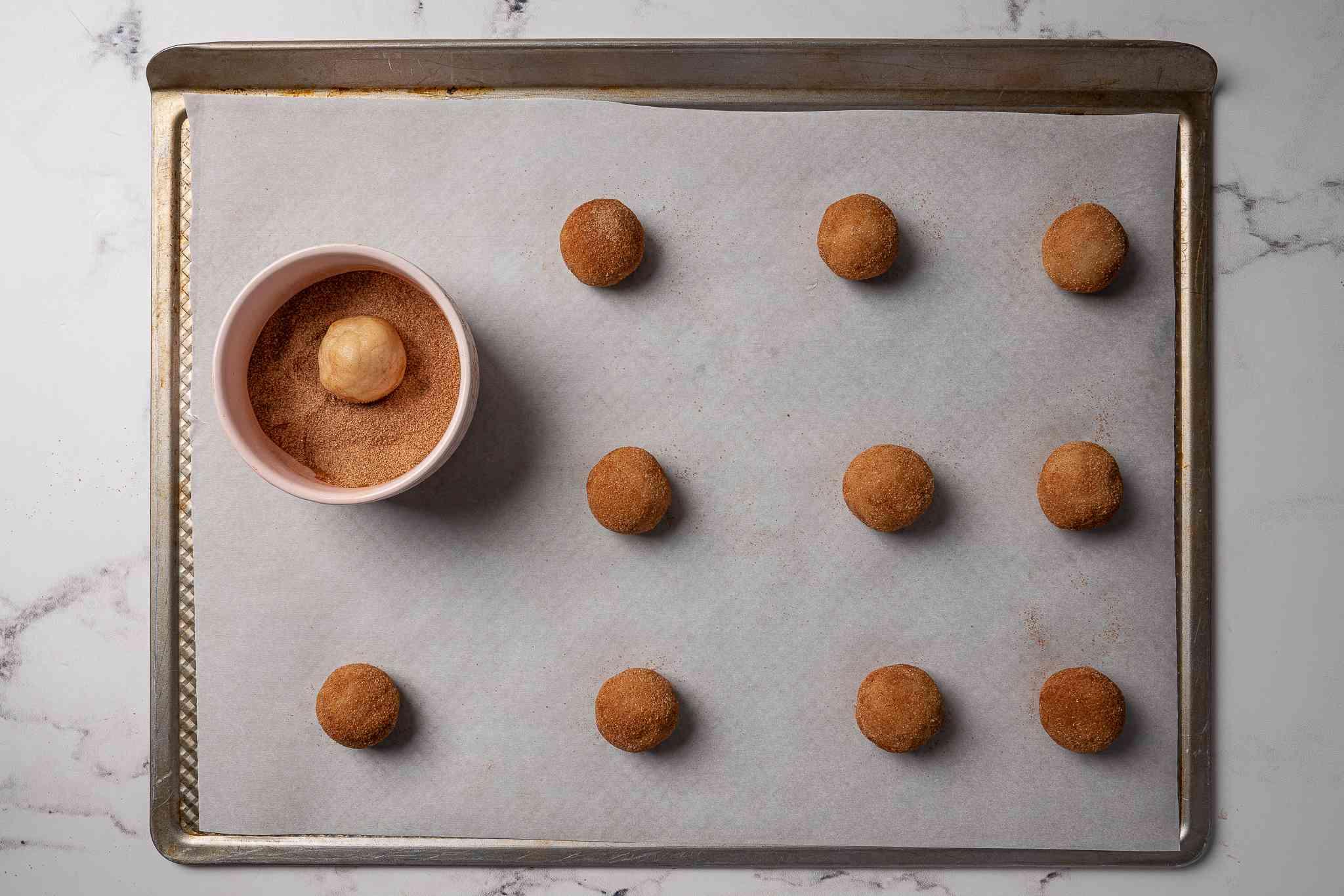 Balls of vegan snickerdoodle dough being rolled in cinnamon sugar
