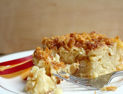 A slice of Jewish noodle kugel made with cottage cheese and garnished with apple slices on a plate.