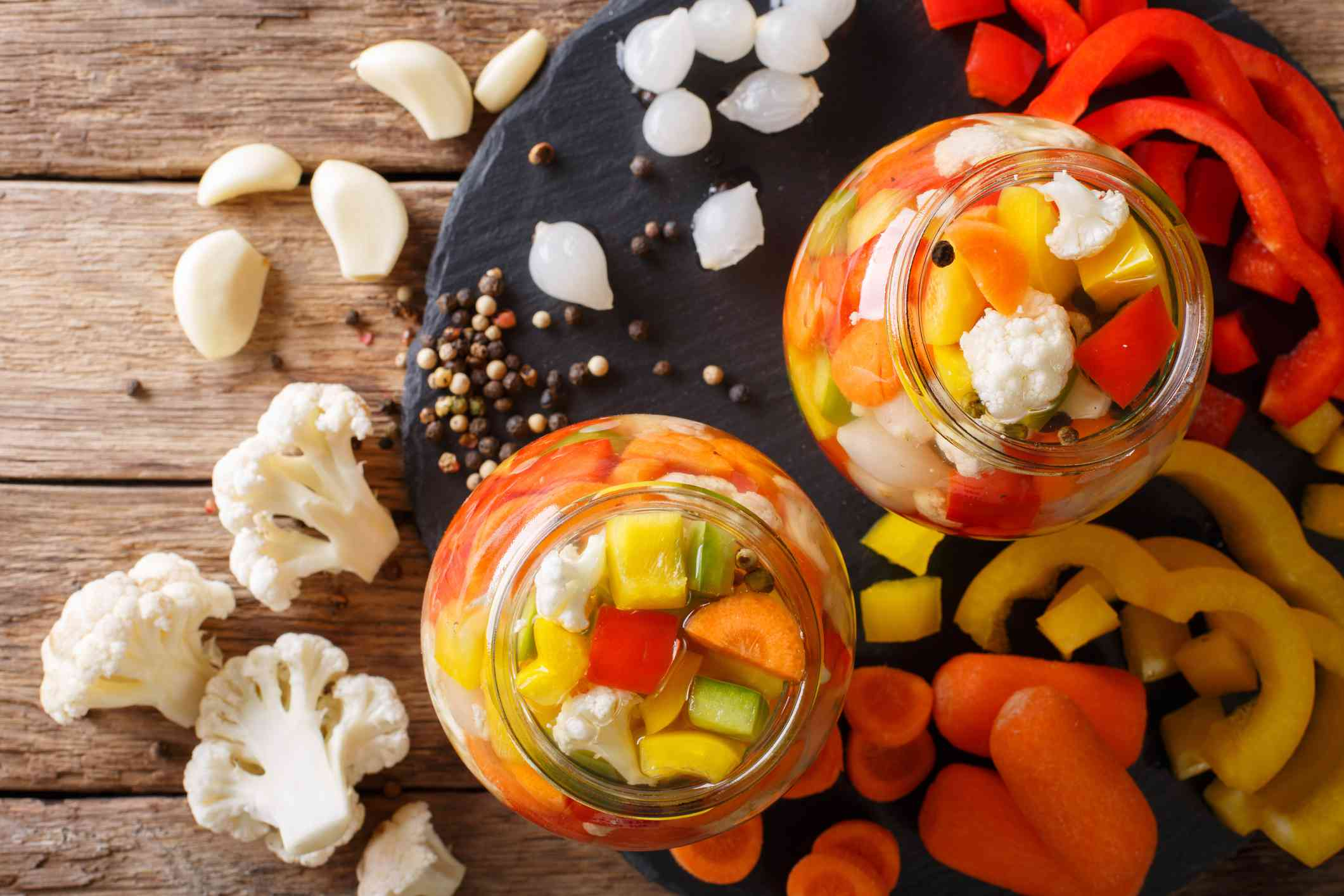 Giardiniera salad from pickled cauliflower, pepper and carrots in glass jars