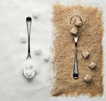 White and brown sugar with spoons.