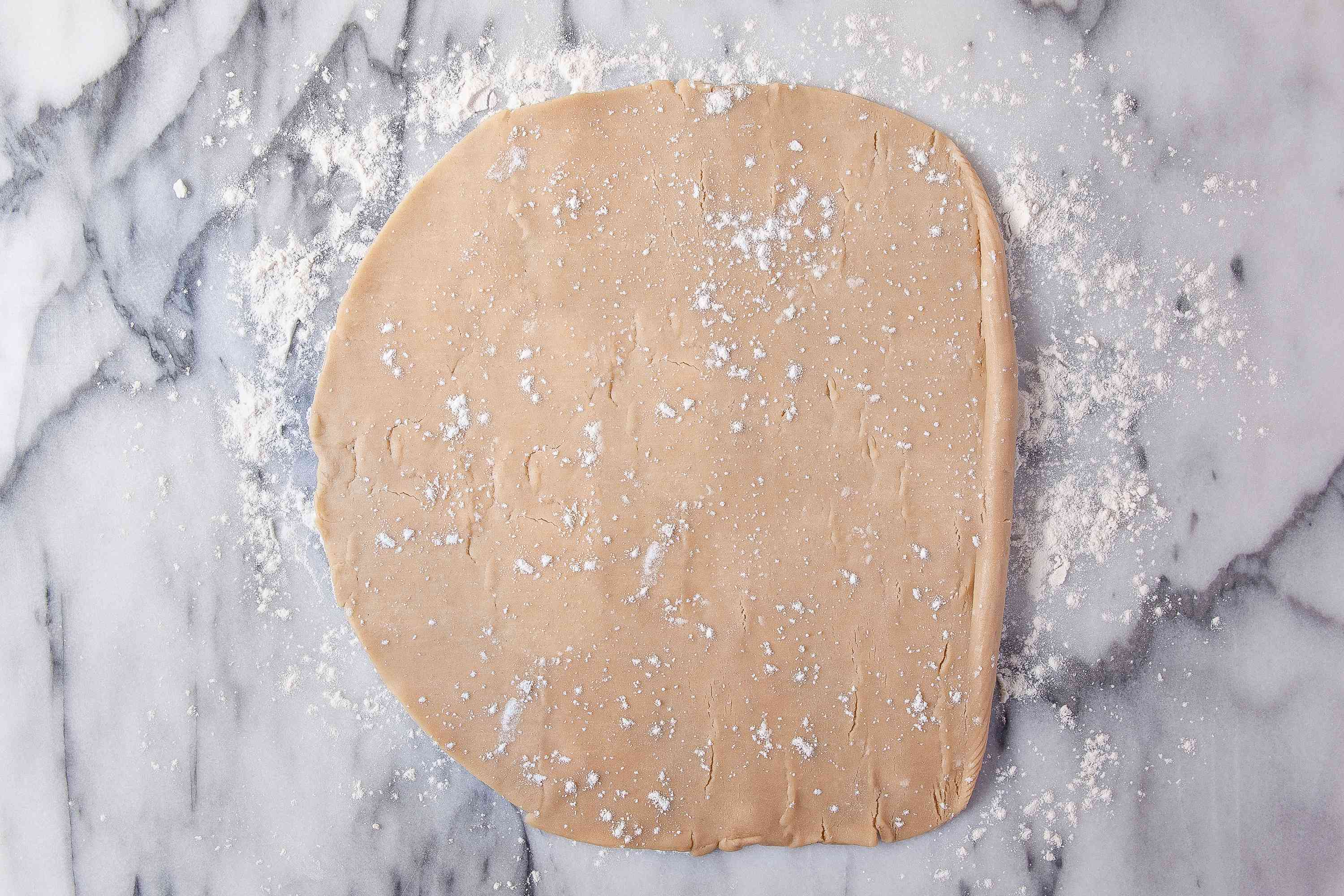 Pie crust with flour on a marble surface