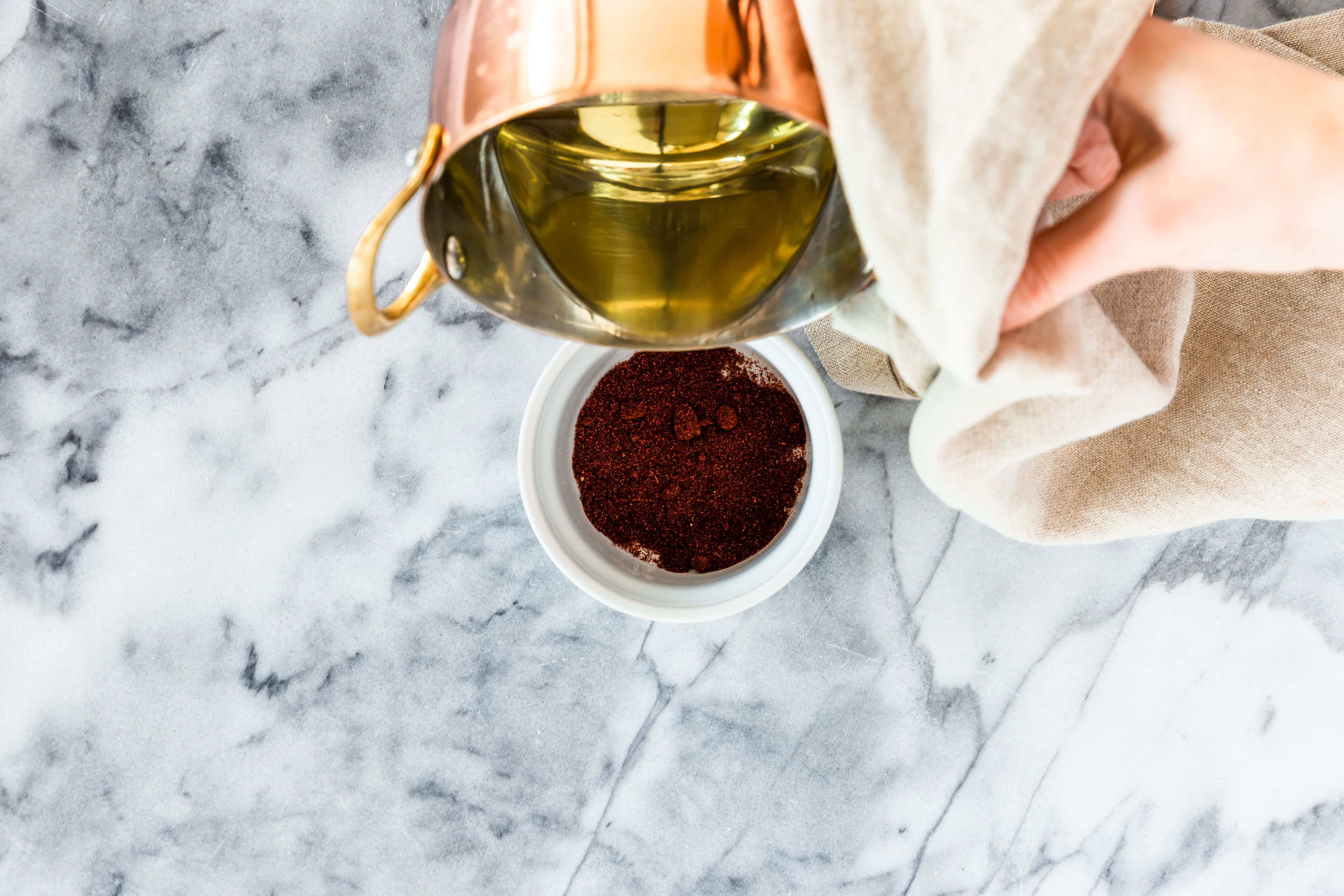 Pouring oil into the cup of chili powder