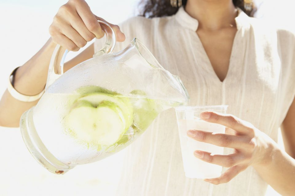 A woman pouring fruit water into a glass