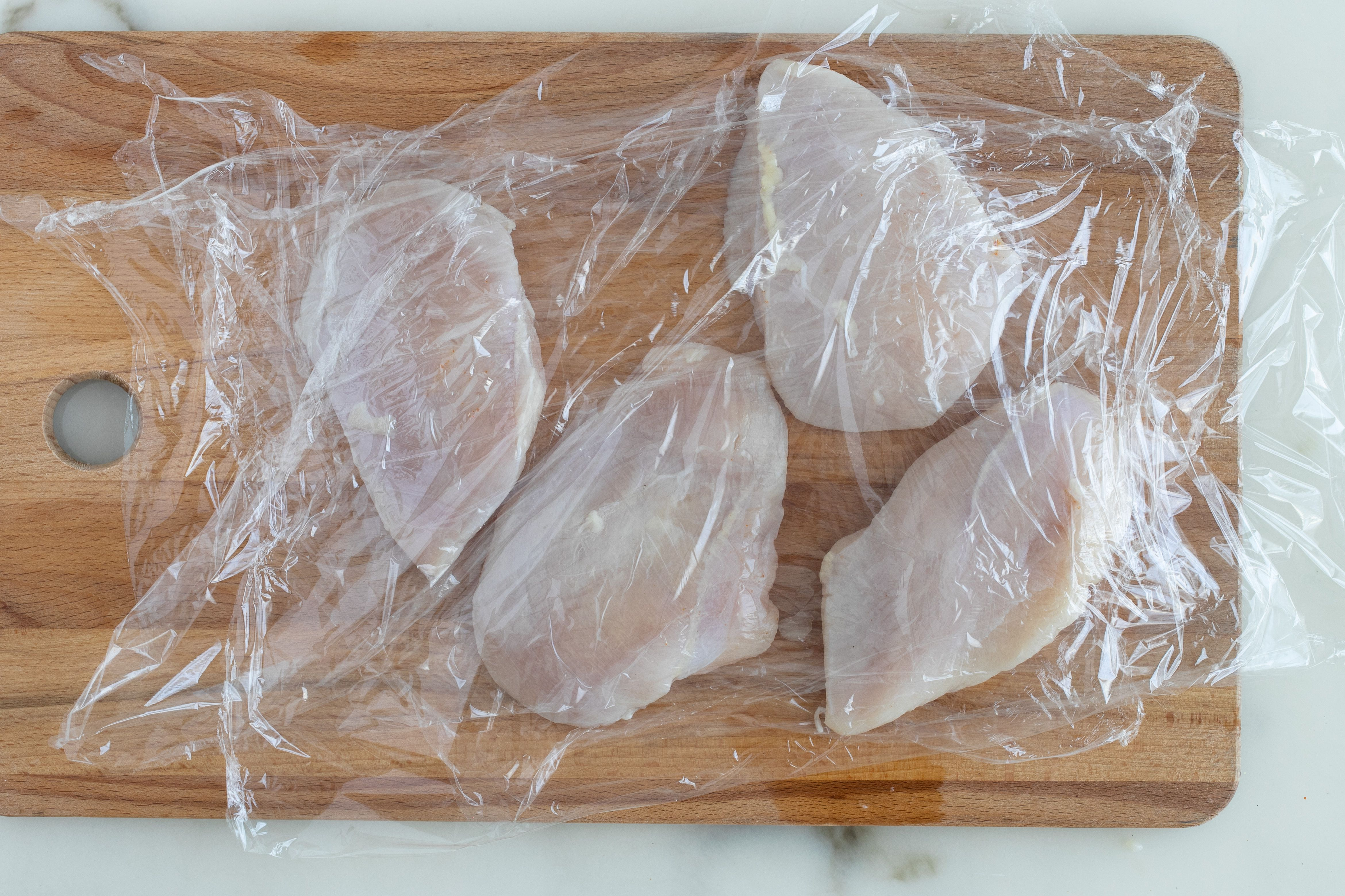 Plastic on chicken breast for pounding