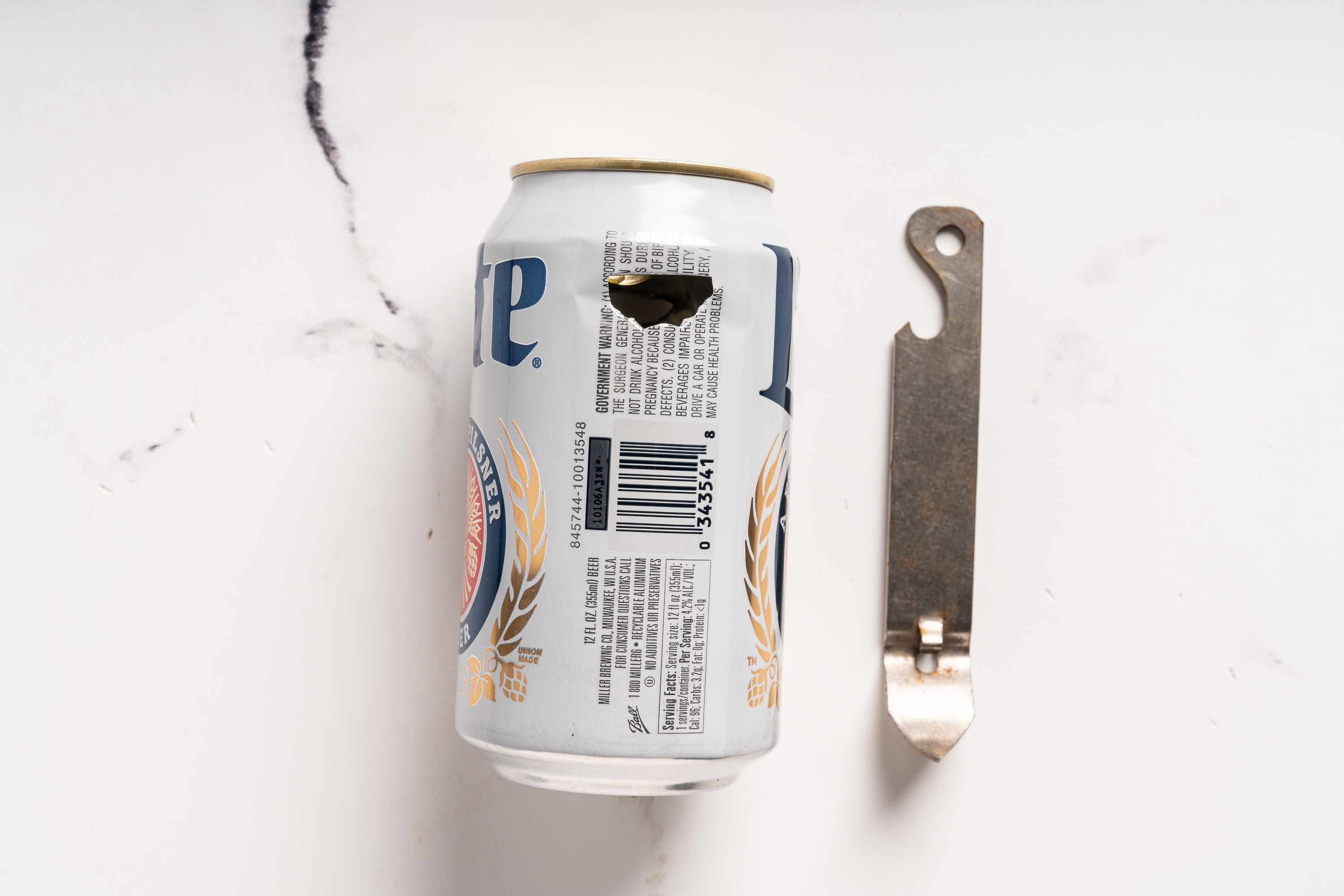 Using a pointed can opener, punch 5 holes around the outside lid of an empty beer can