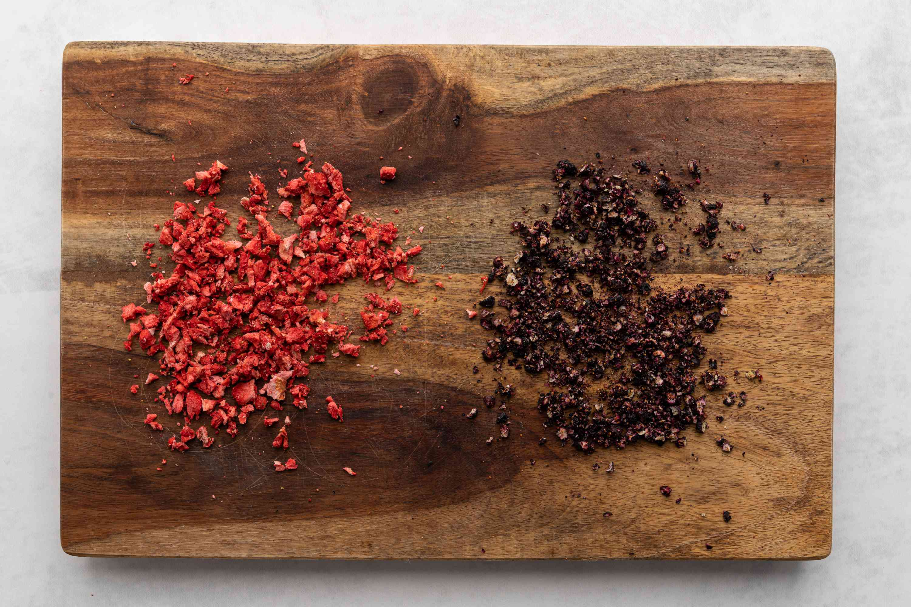 Finely chopped freeze-dried strawberries and blueberries on a cutting board