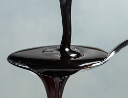 Close-Up Of Syrup Pouring In Spoon Against Gray Background