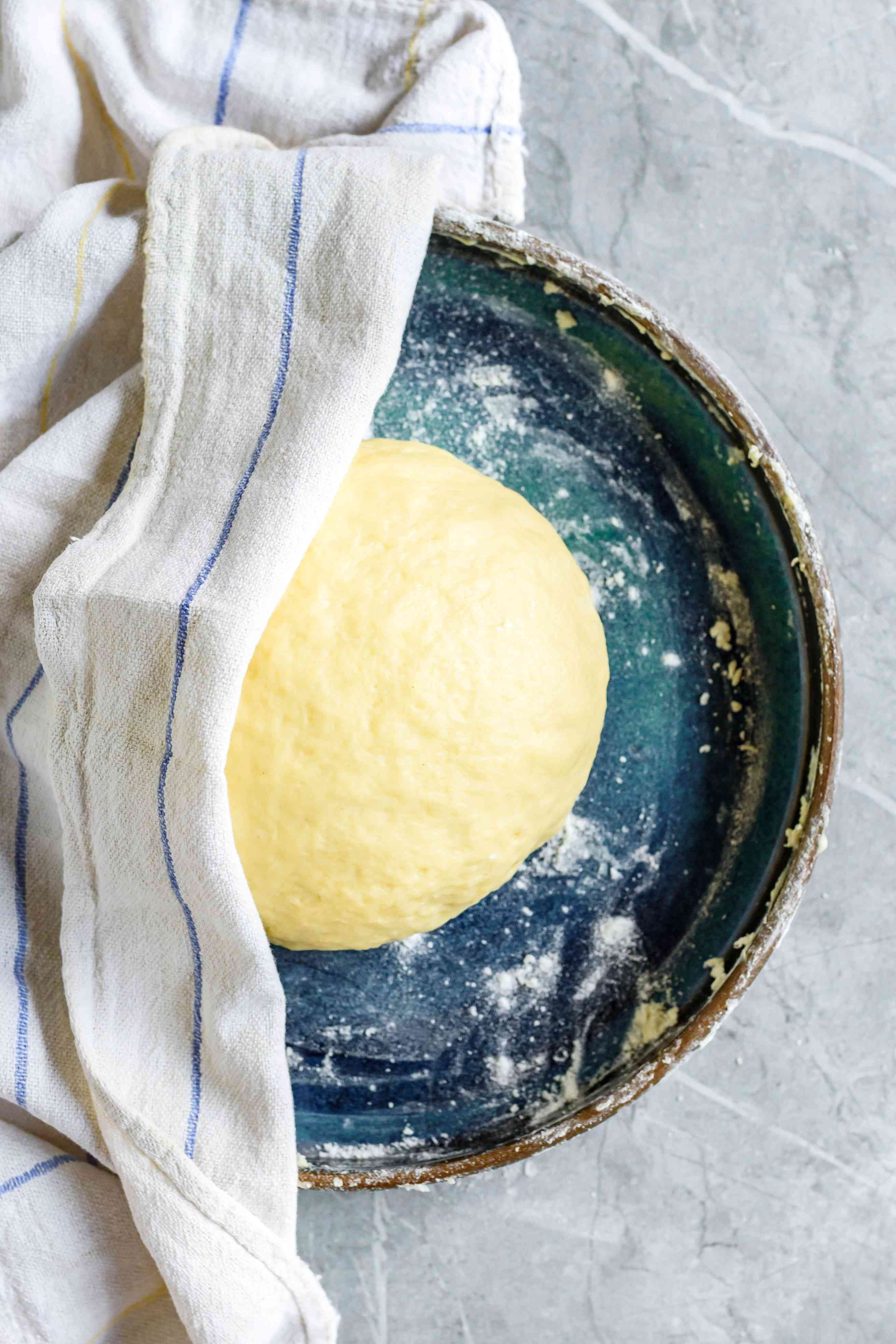 Dough in blue bowl covered by kitchen towel