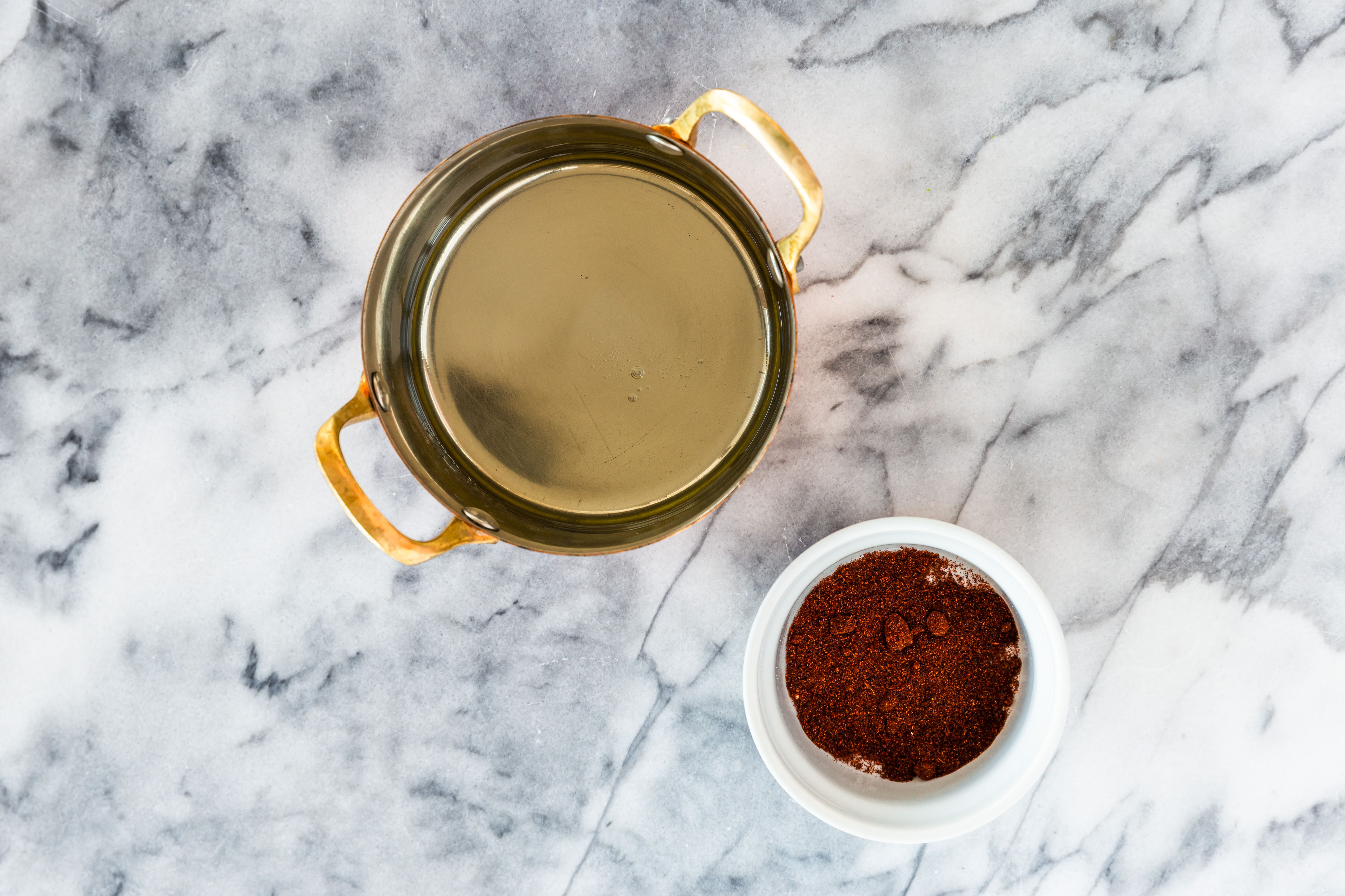 Cooking oil in a pan and a cup of chili powder