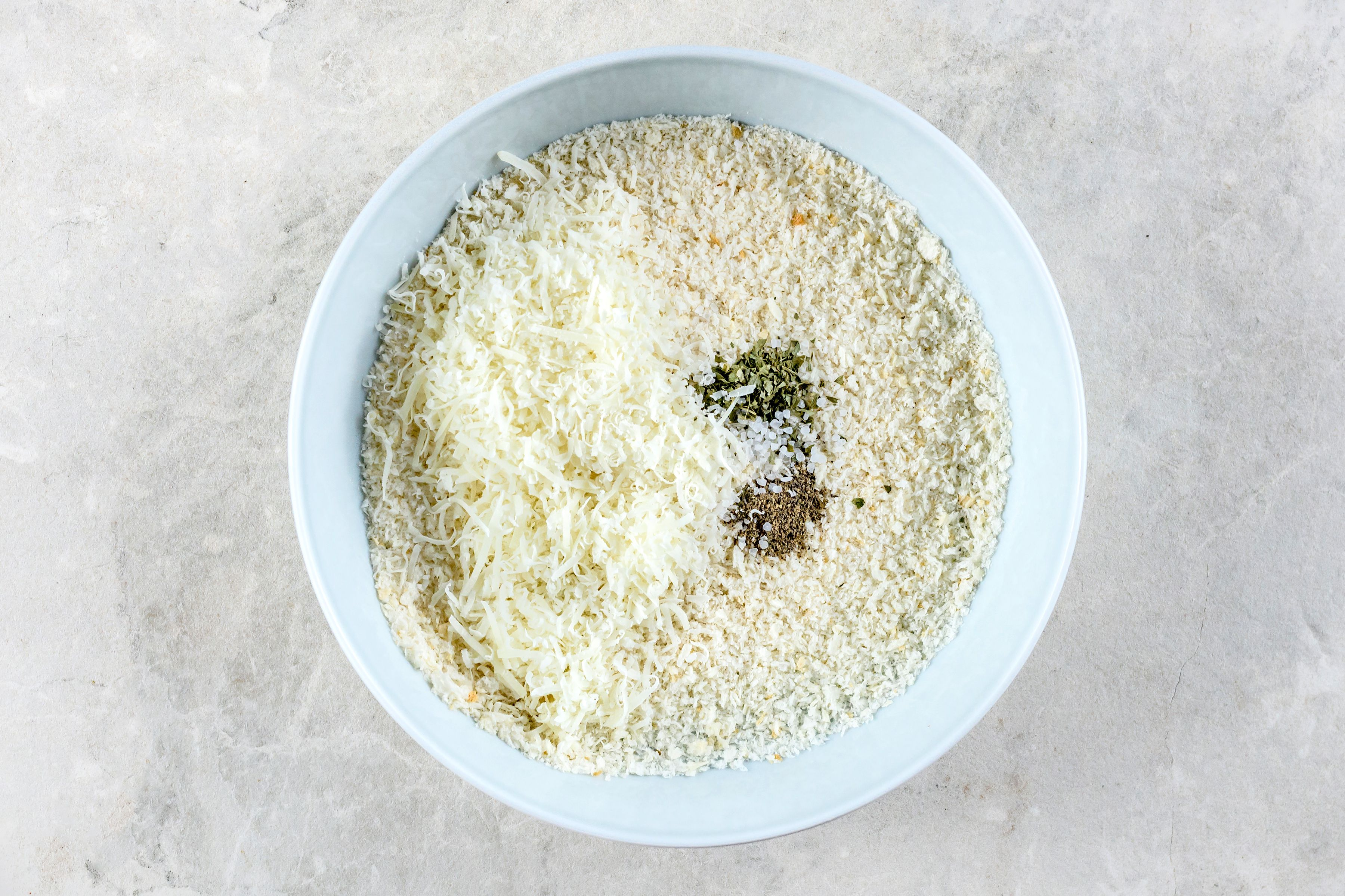 Adding Parmesan cheese, salt, basil, and pepper into breadcrumbs