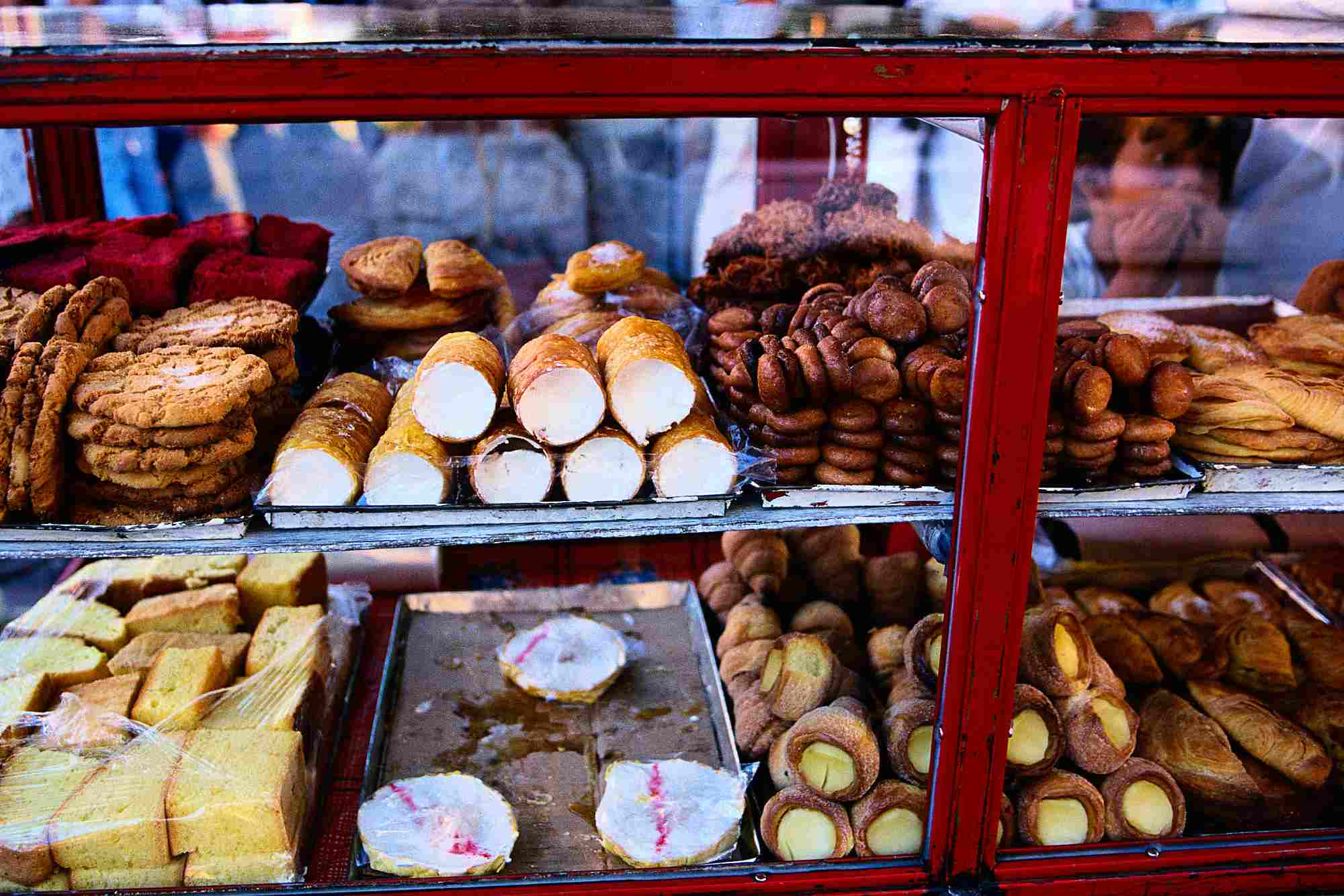 A display case full of a variety of Mexican sweet breads and pastries.