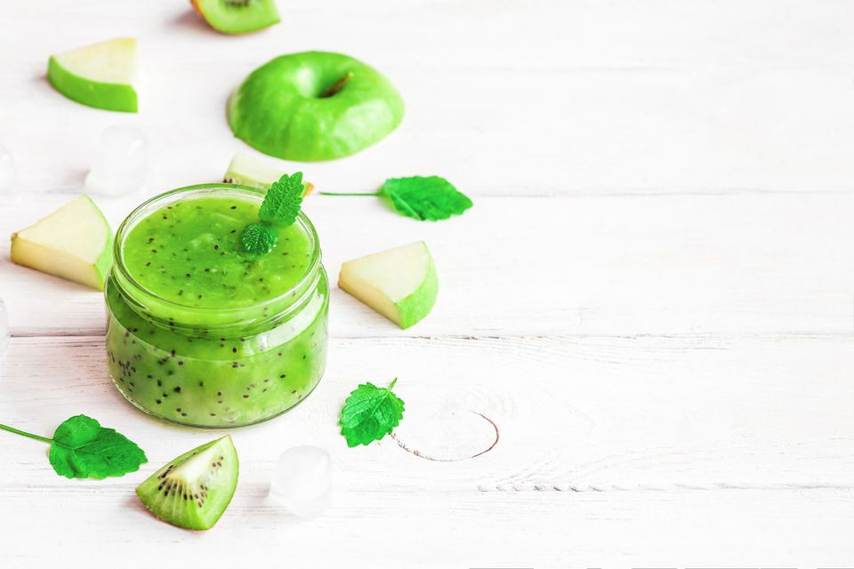 Kiwi apple smoothie decorated with kiwi, apple, and herbs