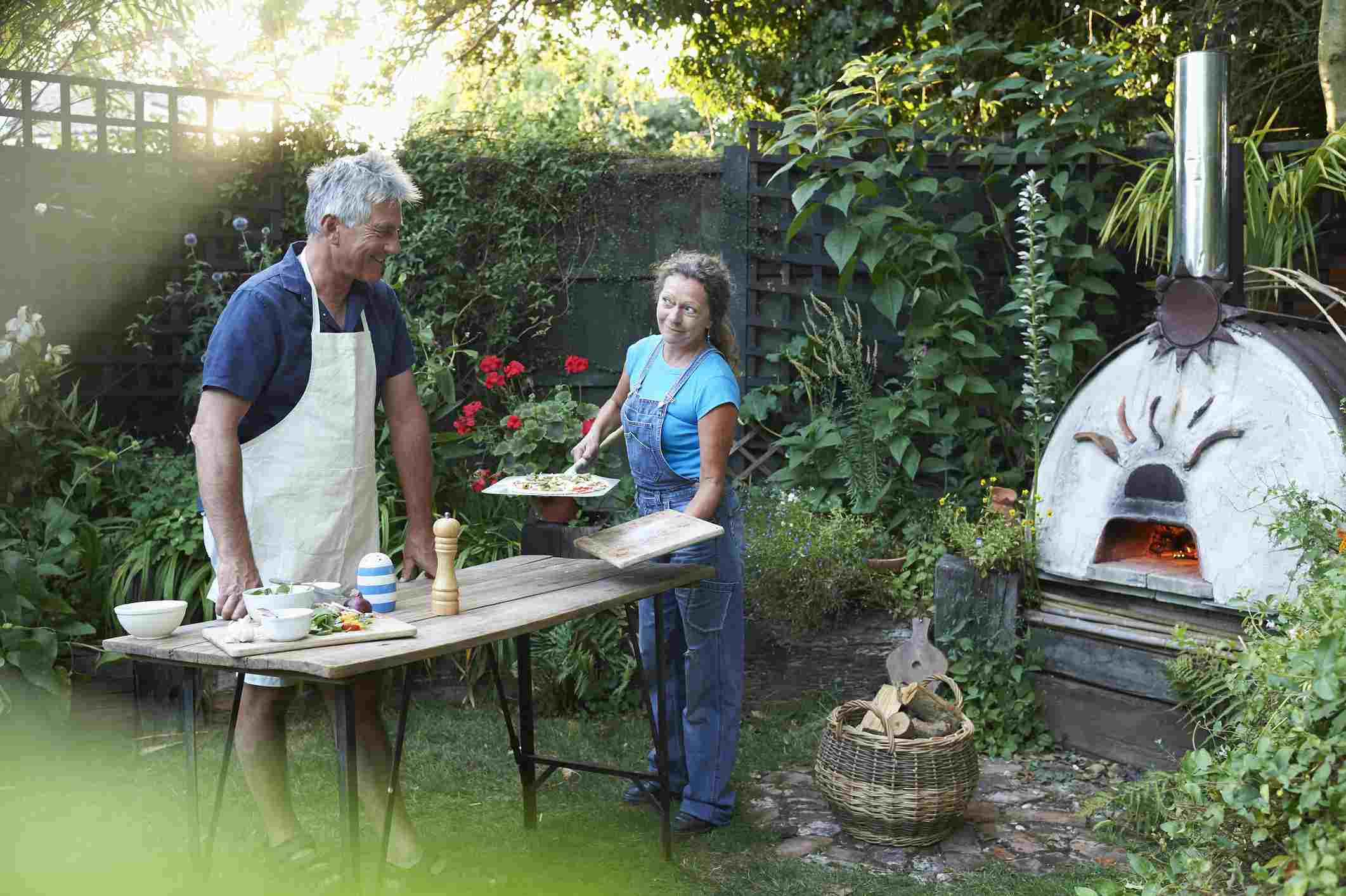 couple making pizza in backyard pizza oven