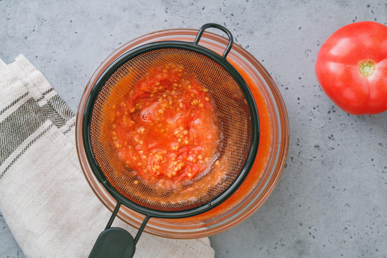 Tomato puree draining through a colander