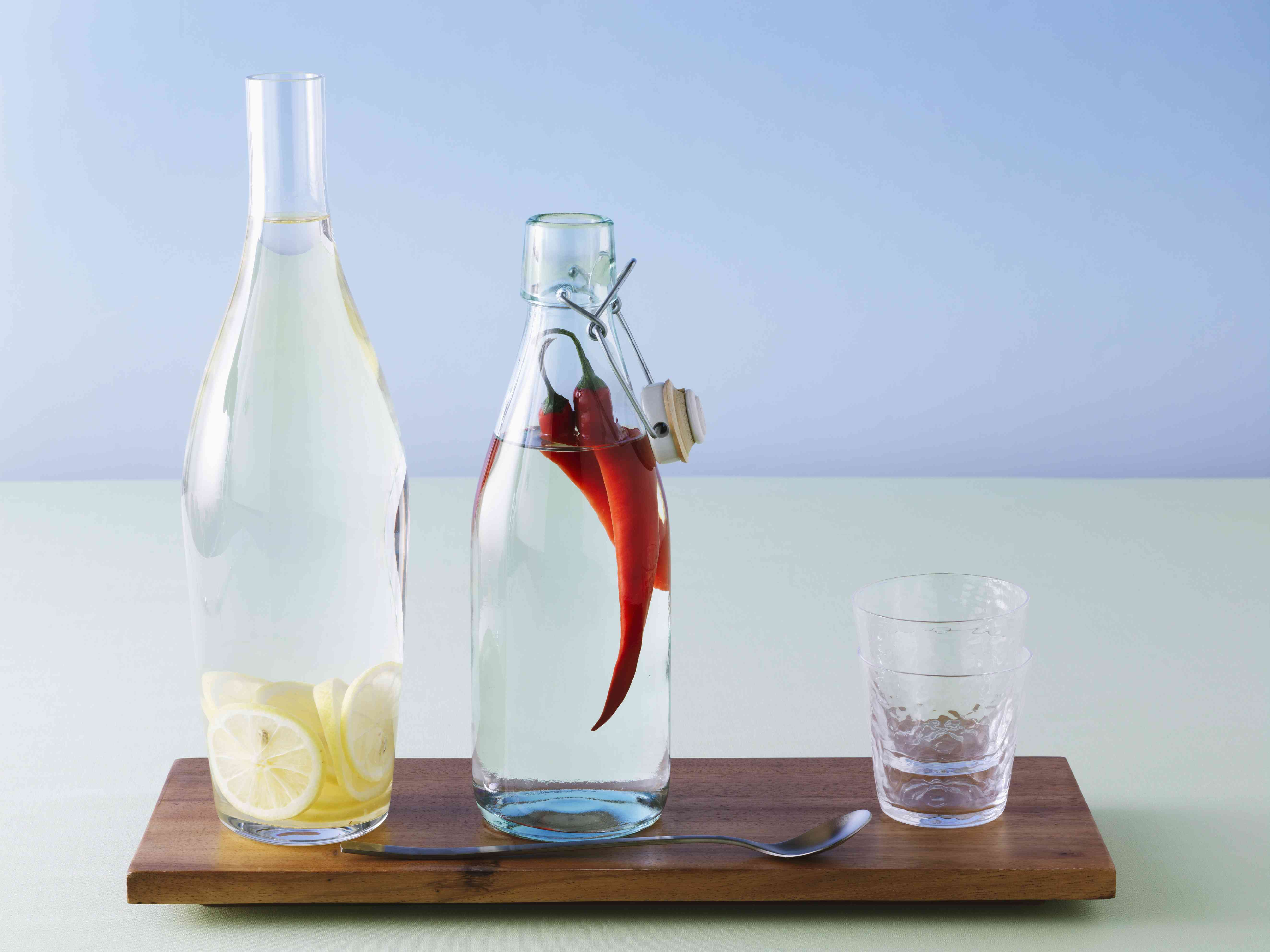 Bottled vodka infusions on a wooden board with a spoon and cup