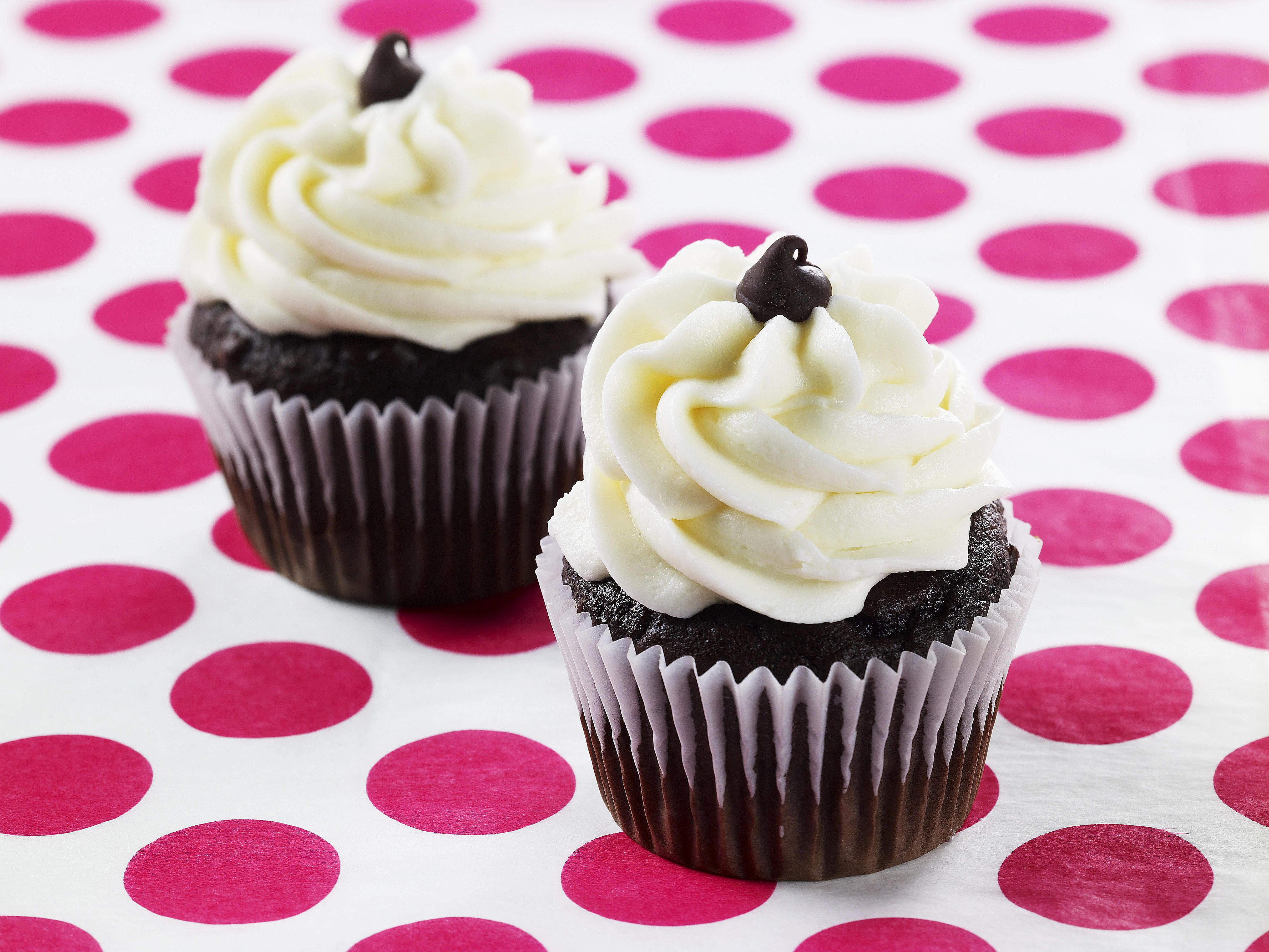 Two velvet cupcakes with icing on spotted surface
