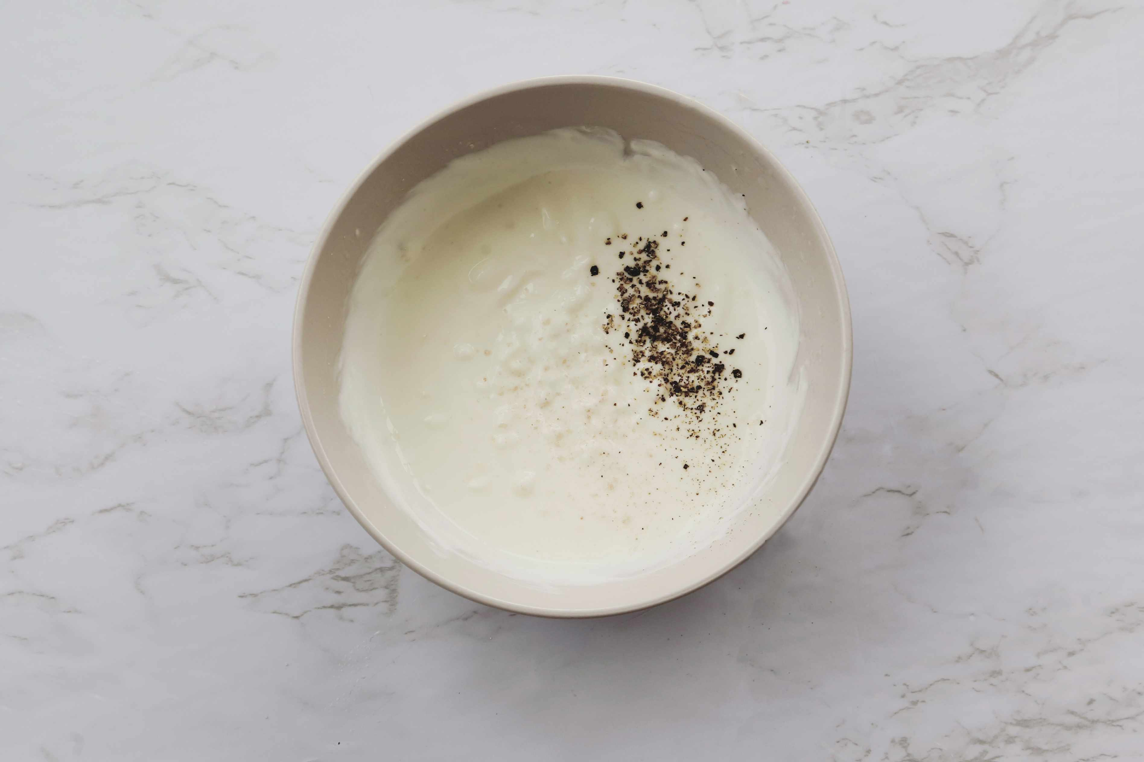 salt and pepper added to the garlic, yogurt and lemon mixture, Garlic Yogurt Salad Dressing