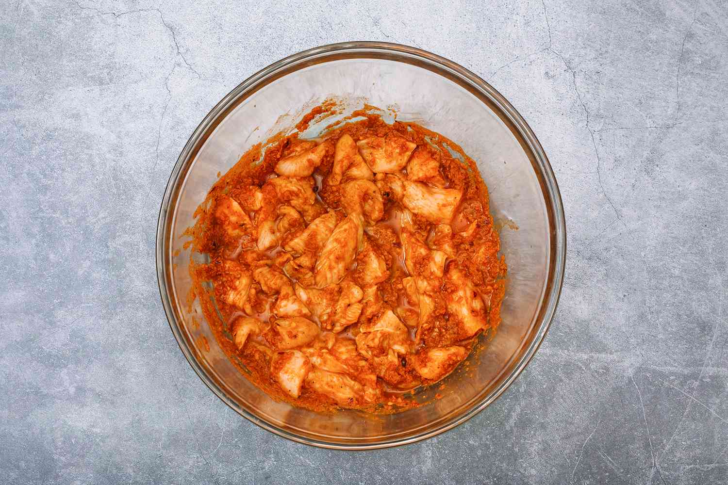 Place the paste into a glass bowl, add the vinegar and the chicken