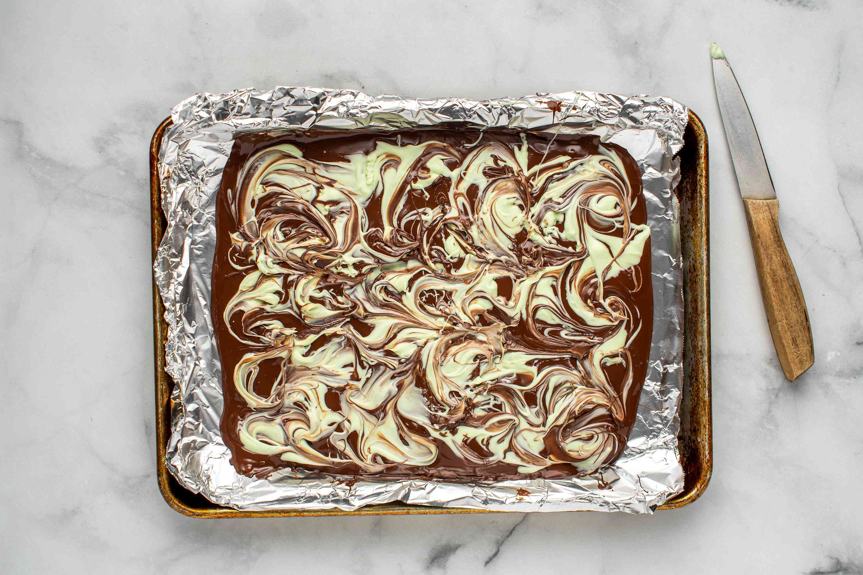 dark and white chocolate swirled together on a baking sheet