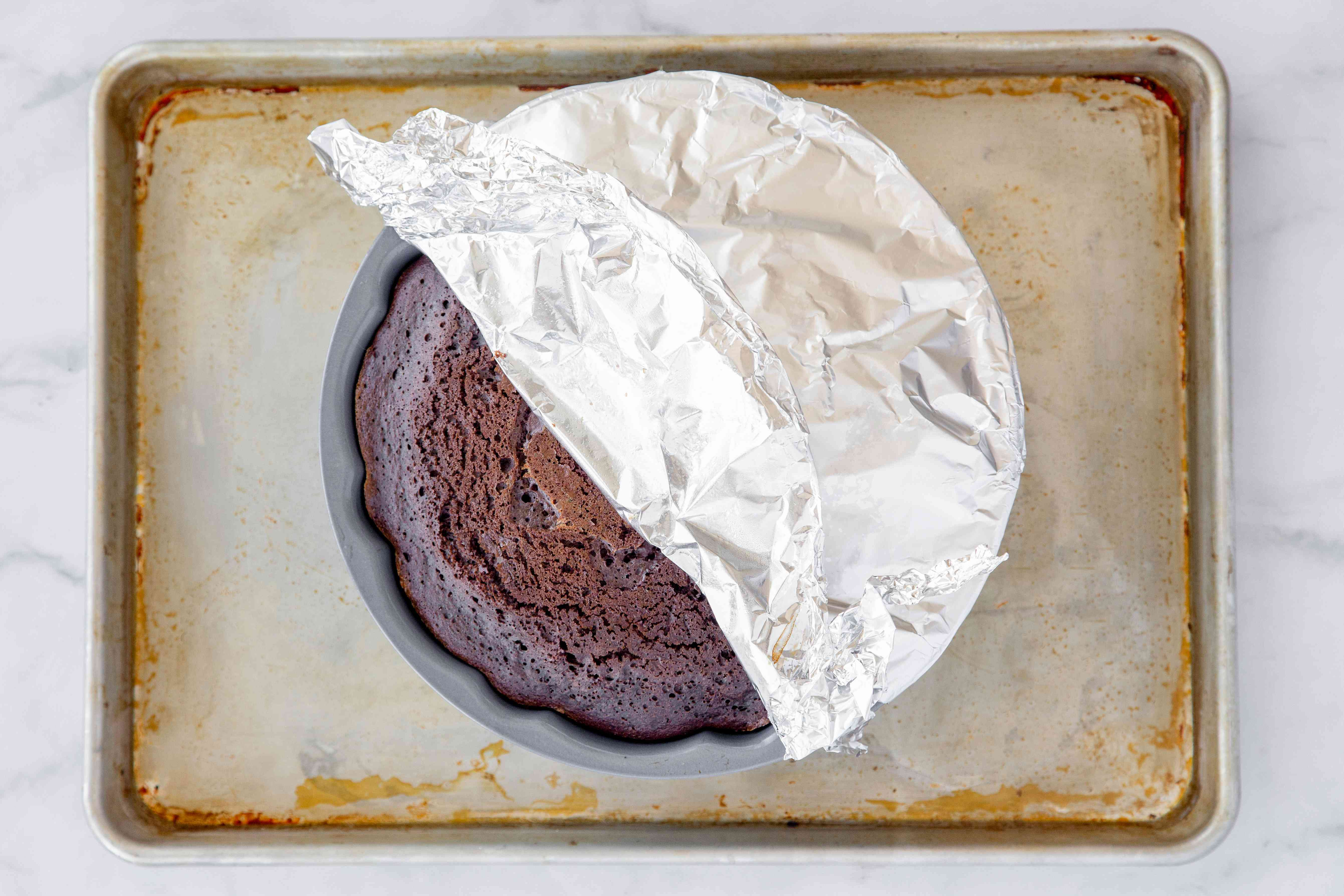 baked cake in a bunt pan covered with aluminum foil on a baking sheet
