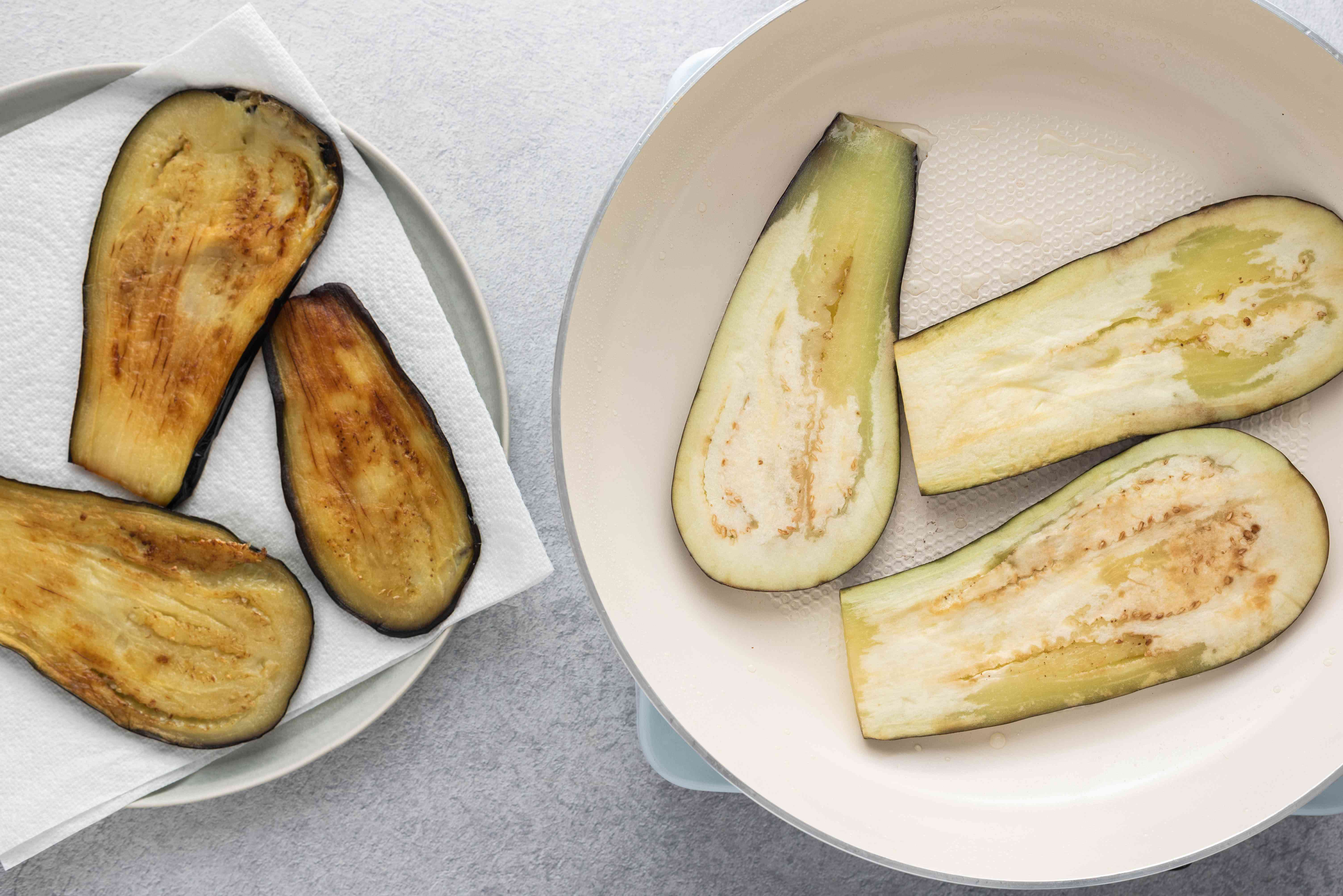 eggplant cooking in a frying pan, cooked eggplant on a paper towel lined plate