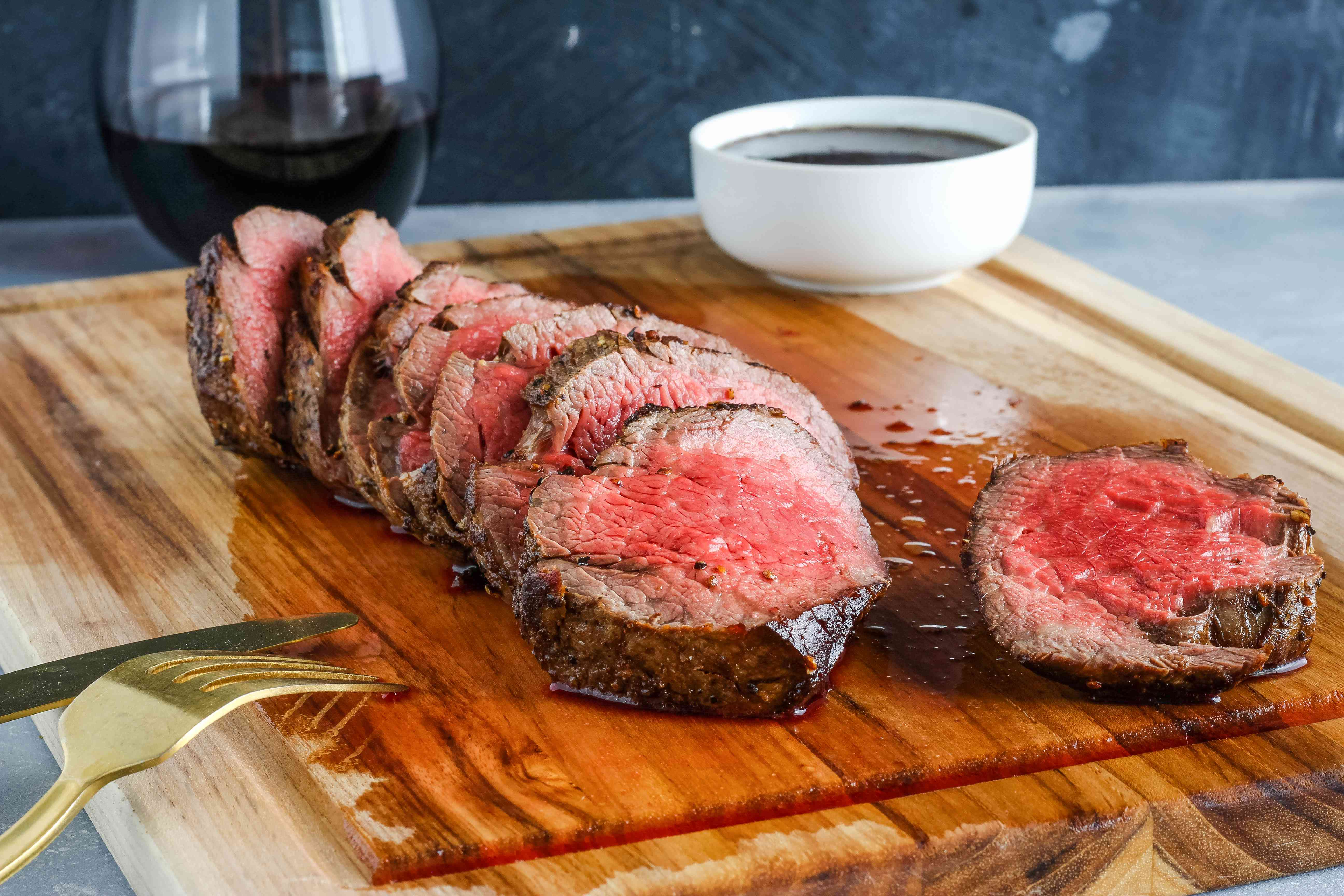 Cooked chateaubriand sliced on the diagonal plus a bowl of wine sauce