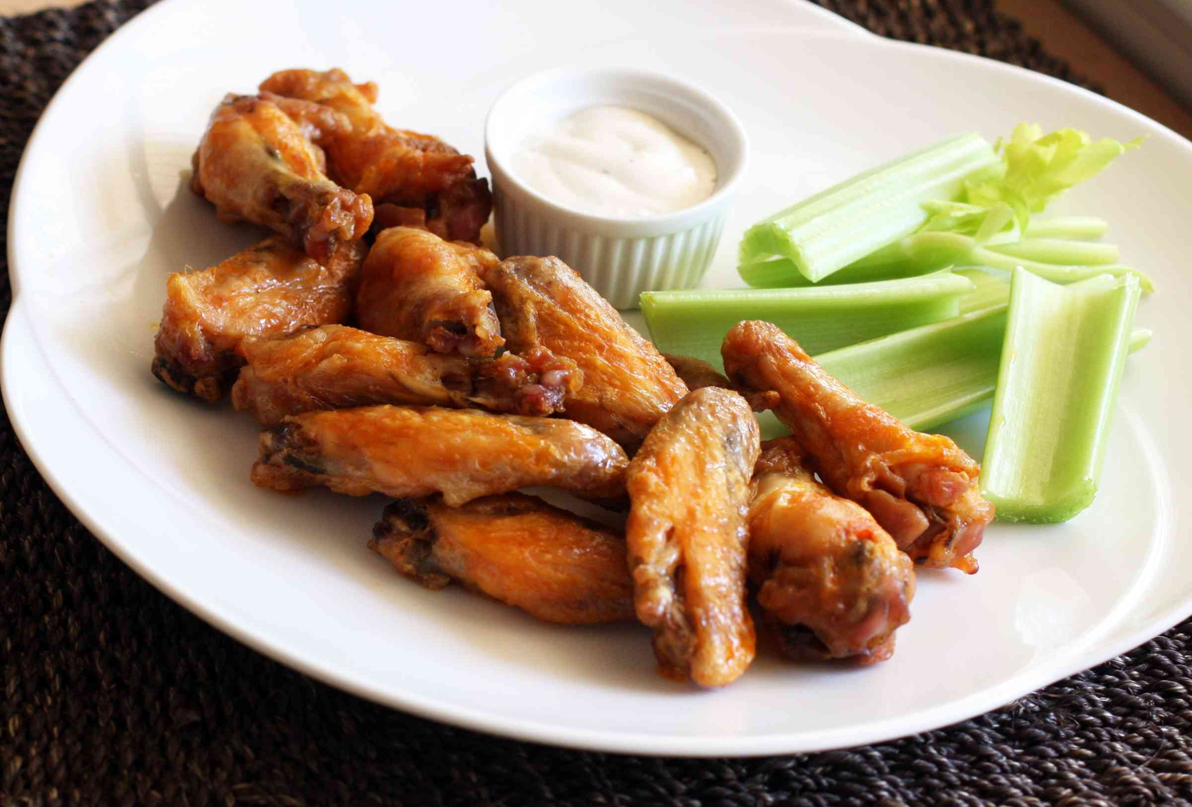 Baked Buffalo chicken wings with celery on a white plate