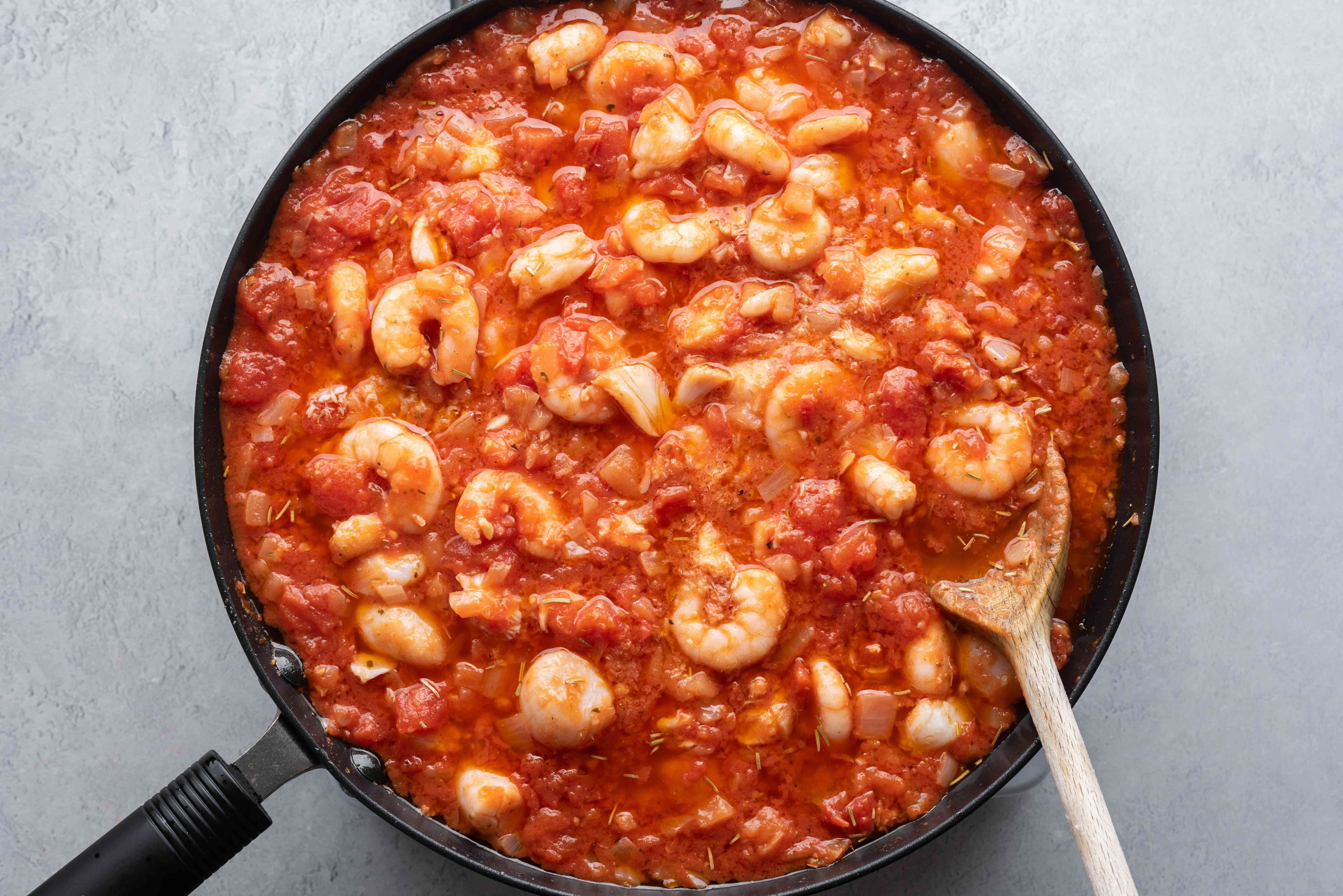 Seafood added to the tomato mixture in the pan
