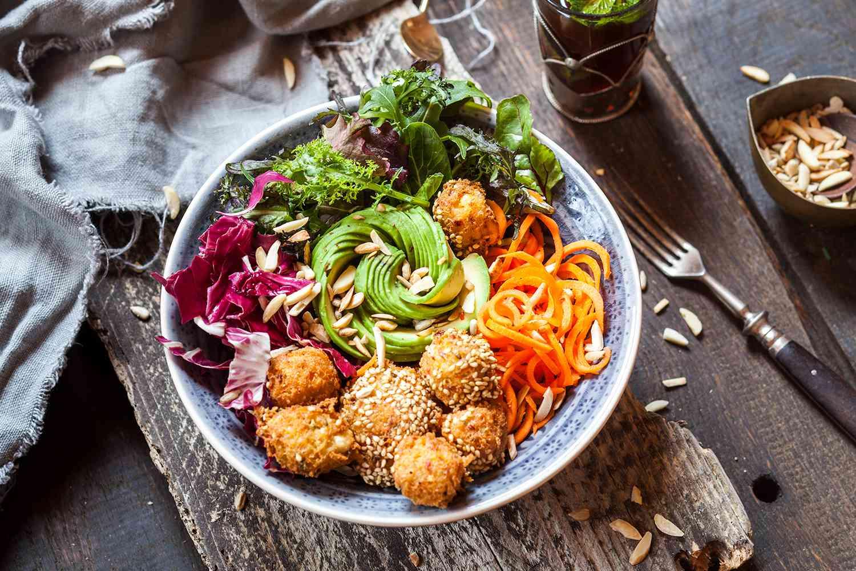 Rainbow salad bowl with carrots, lettuce, avocado, millet falafel and Moroccan mint tea